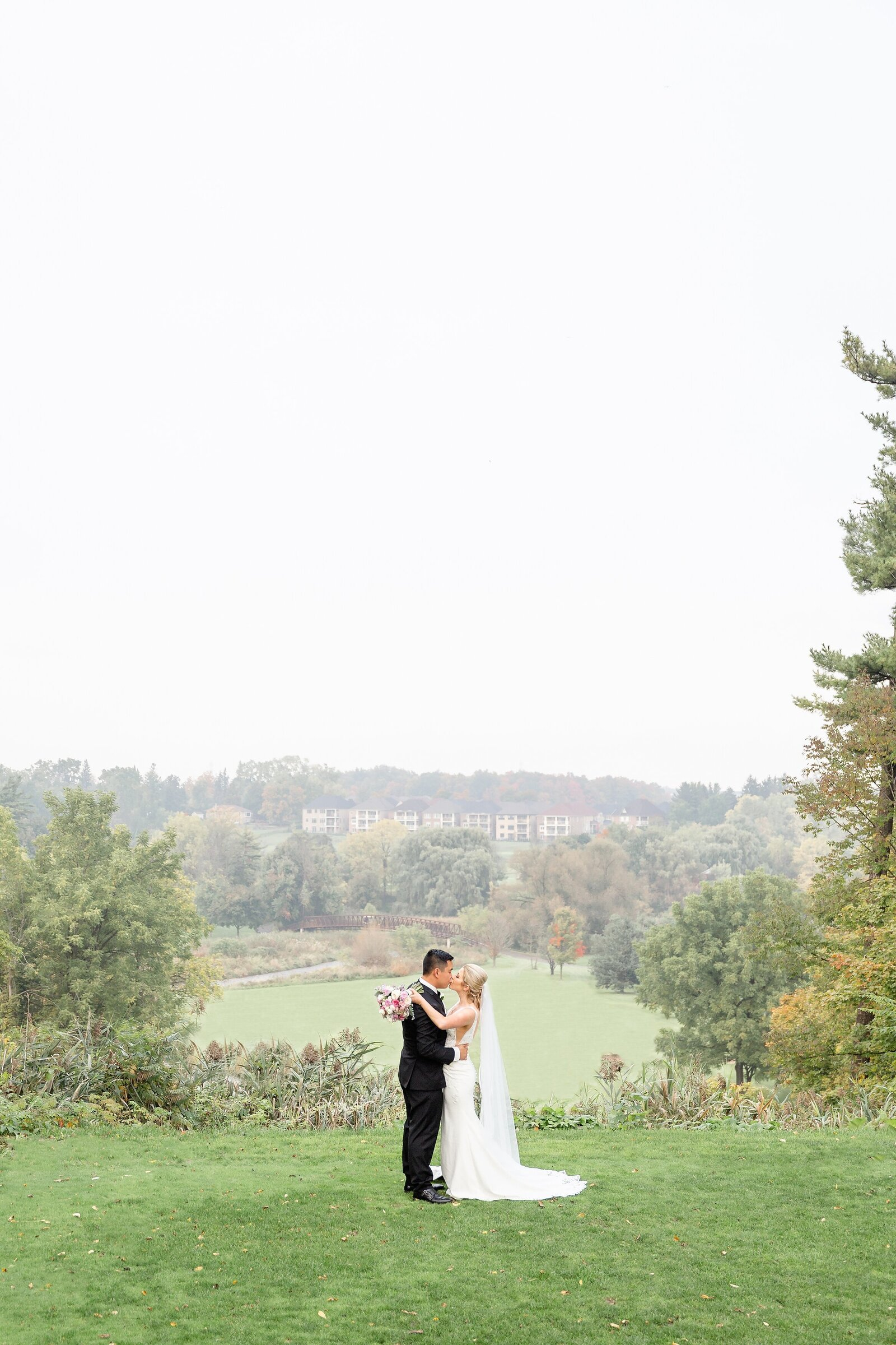 Bride-kissing-her-new-husband-on-a-hill-overlooking-a-beautiful-view-at-lionhead-golf-club