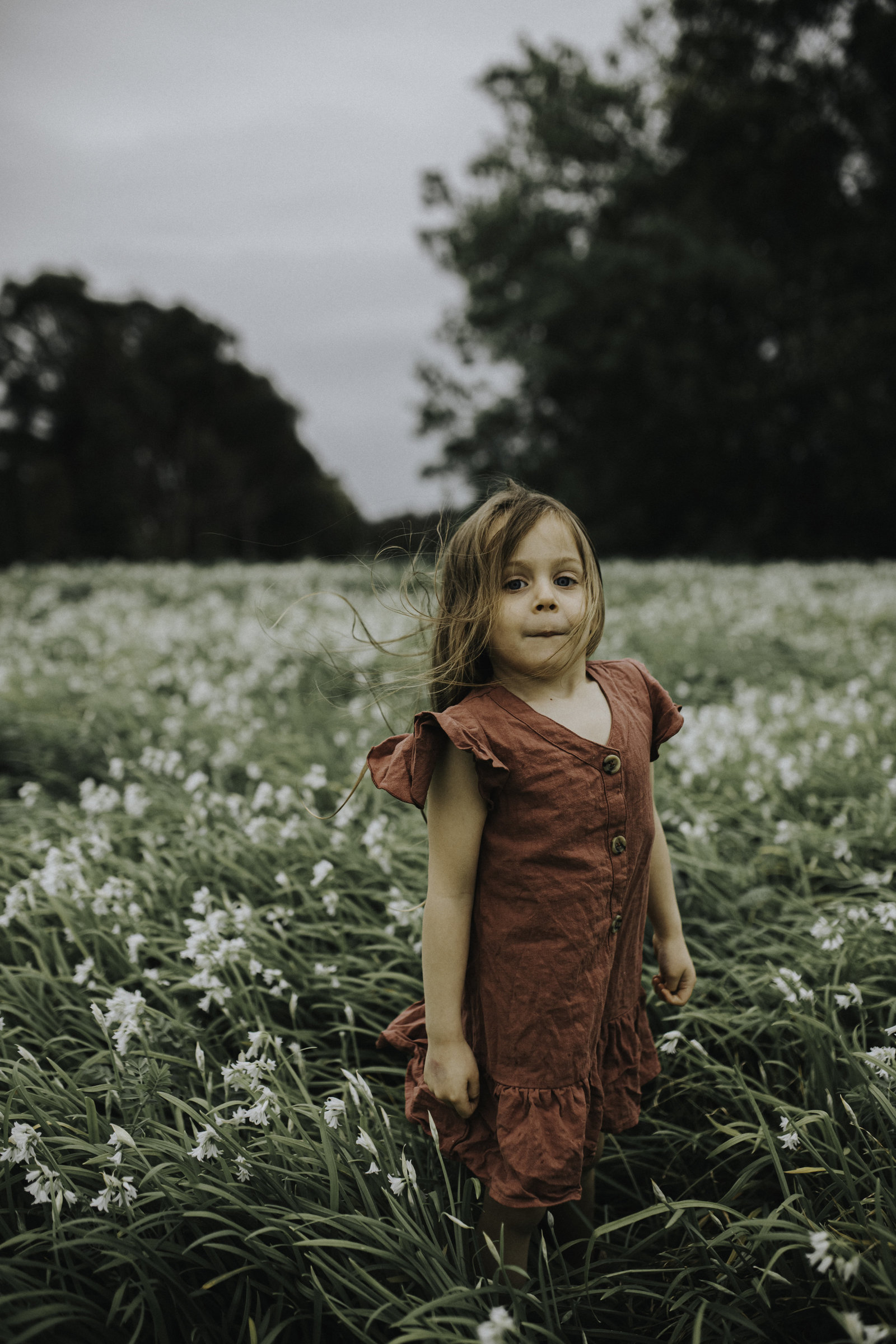 Photo of little girl in field of grass and flowers for Melbourne Family Photography Session with Sapphire and Stone Photography
