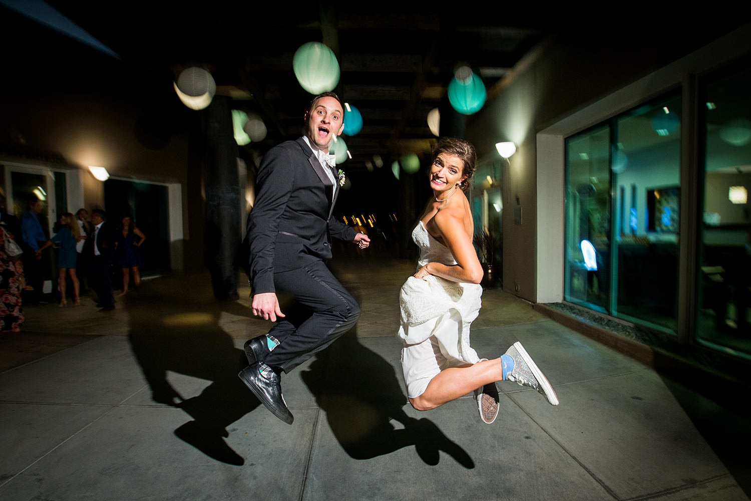 jumping night time shot with bride and groom