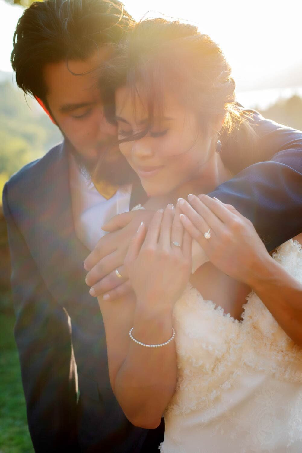 a groom hugs a bride bathed in sunlight with her hair blowing in the wind