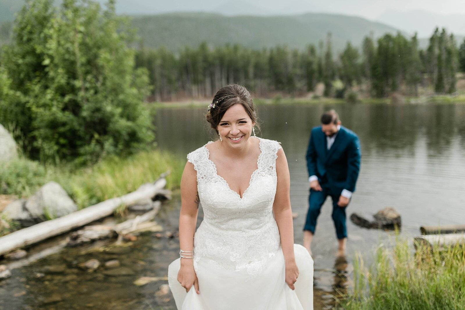 bride and groom wading in water at rocky mountain national park