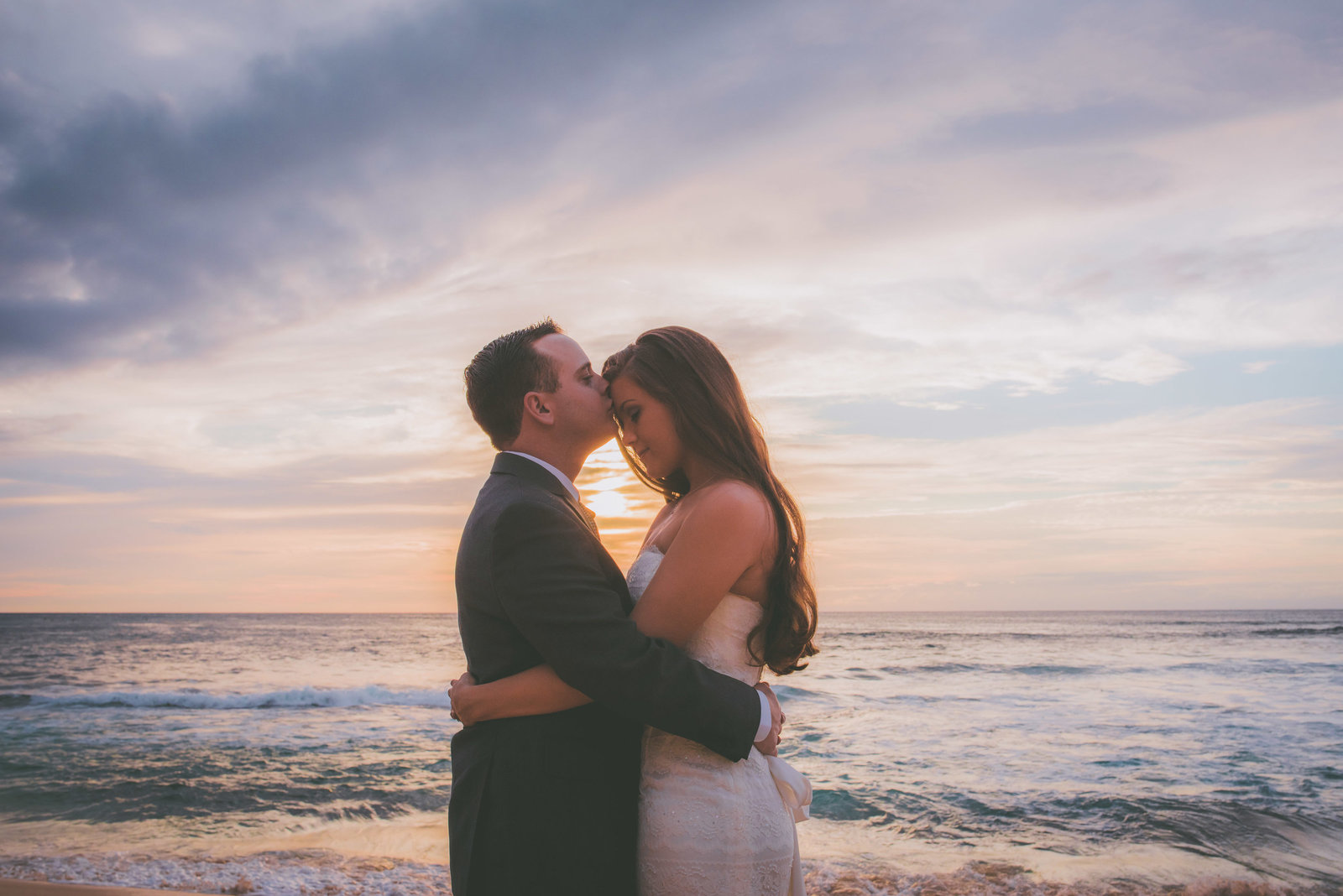 A groom kisses his bride's forehead during sunset on a Oahu beach.