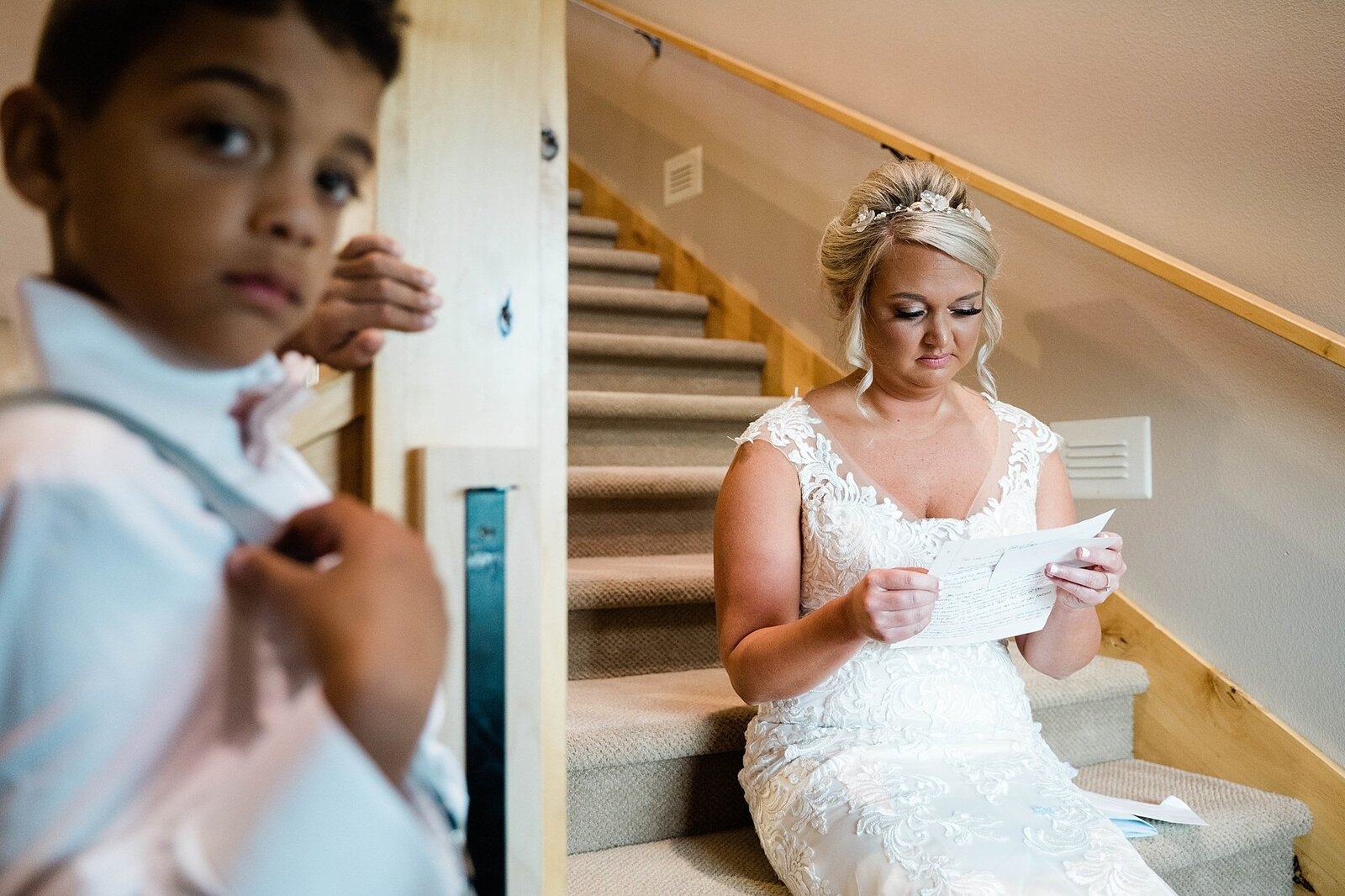 Bride reads letter from her wife to be on the chateau steps in iowa