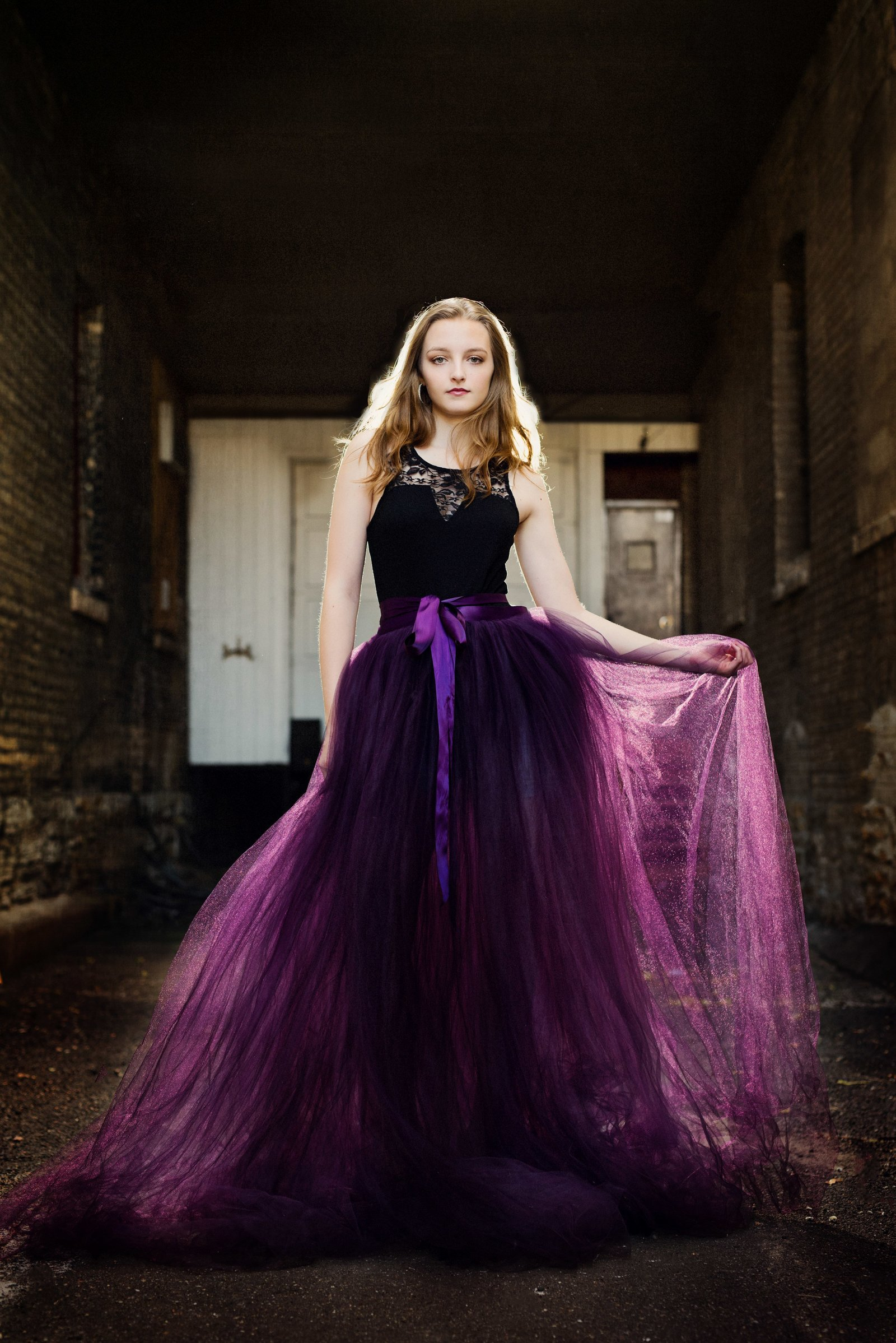 Red carpet style senior picture of girl in gorgeous purple formal dress