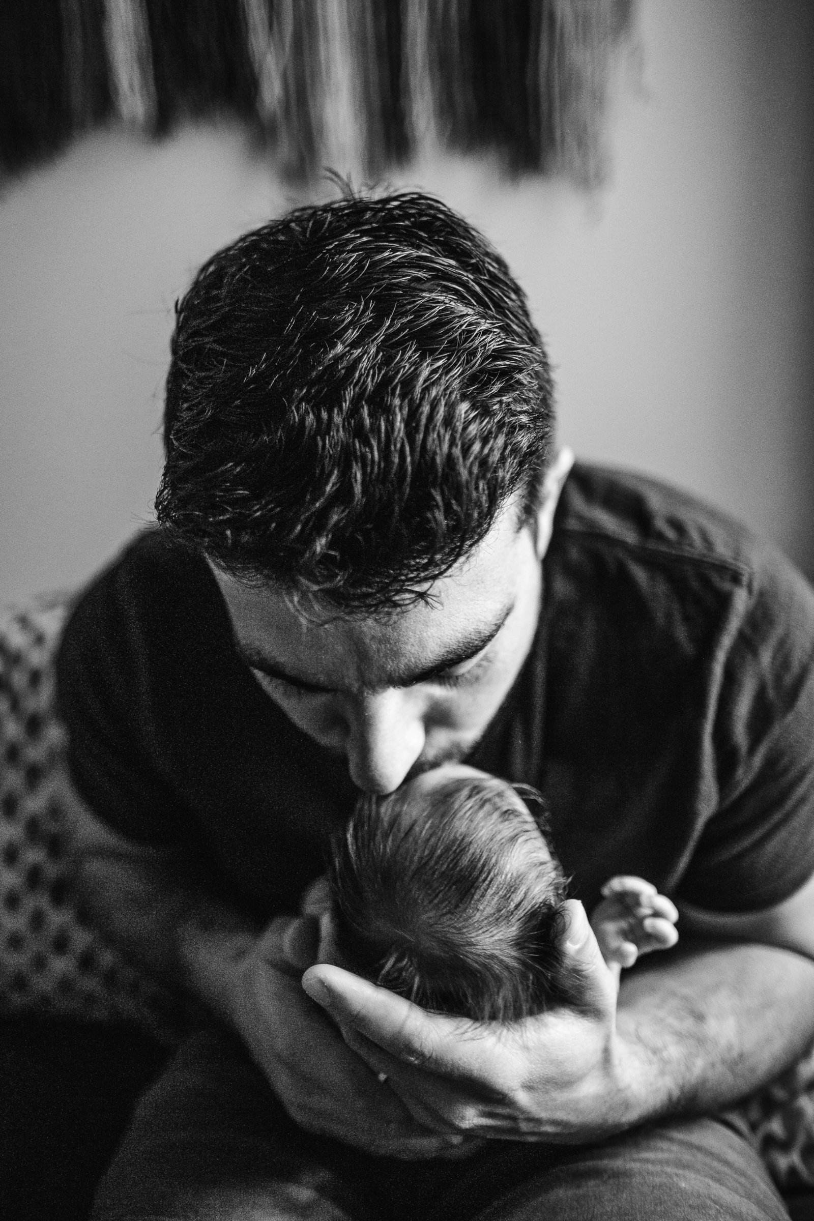 black and white portrait of father in brookline kissing newborn baby head