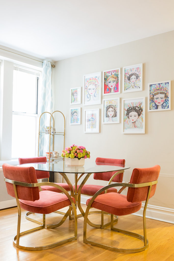 A glass table with orange in gold chairs  and paintings of empowering women.