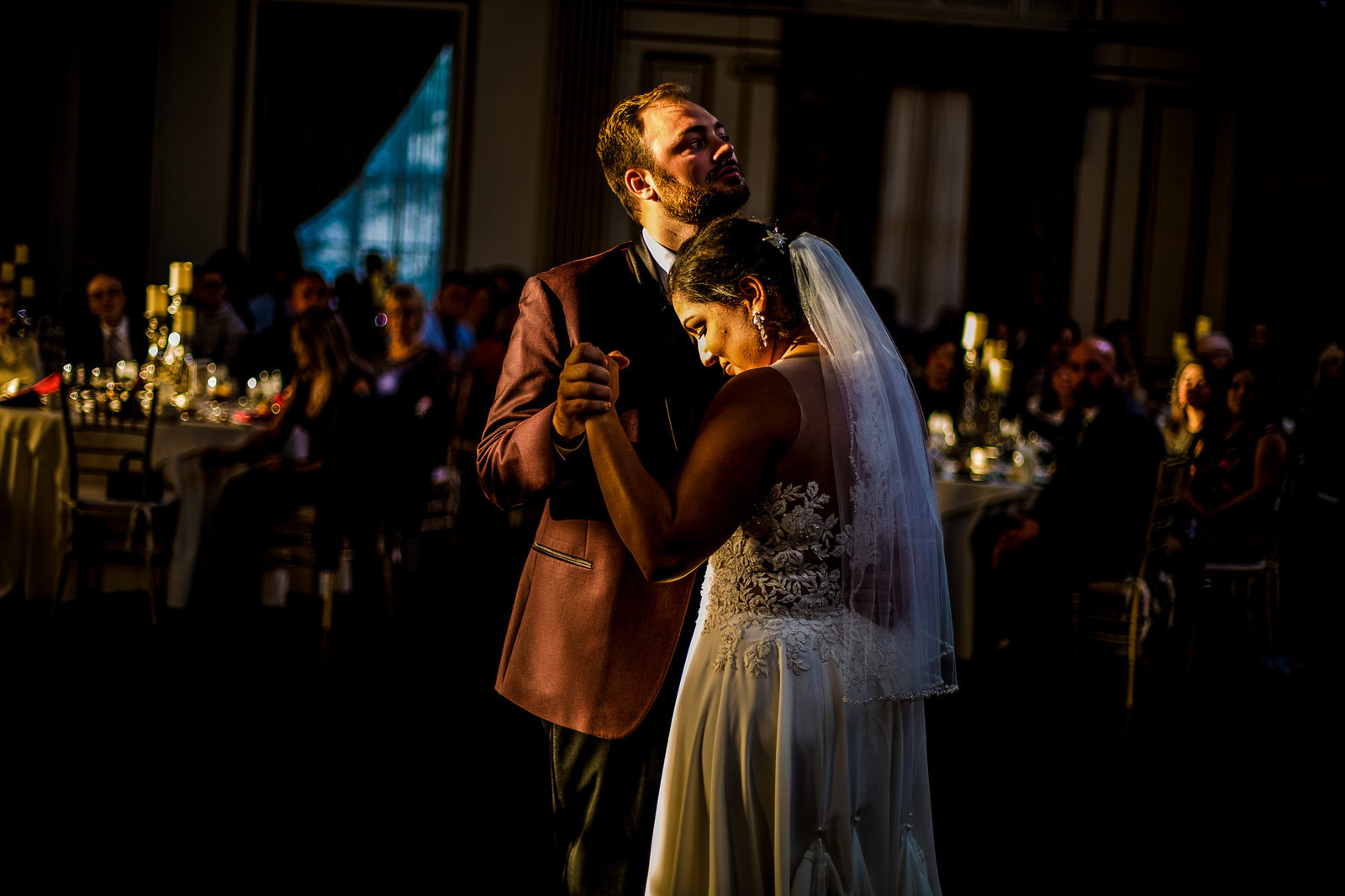 Bride and groom dance while framed in light of setting sun at the George Washington Hotel