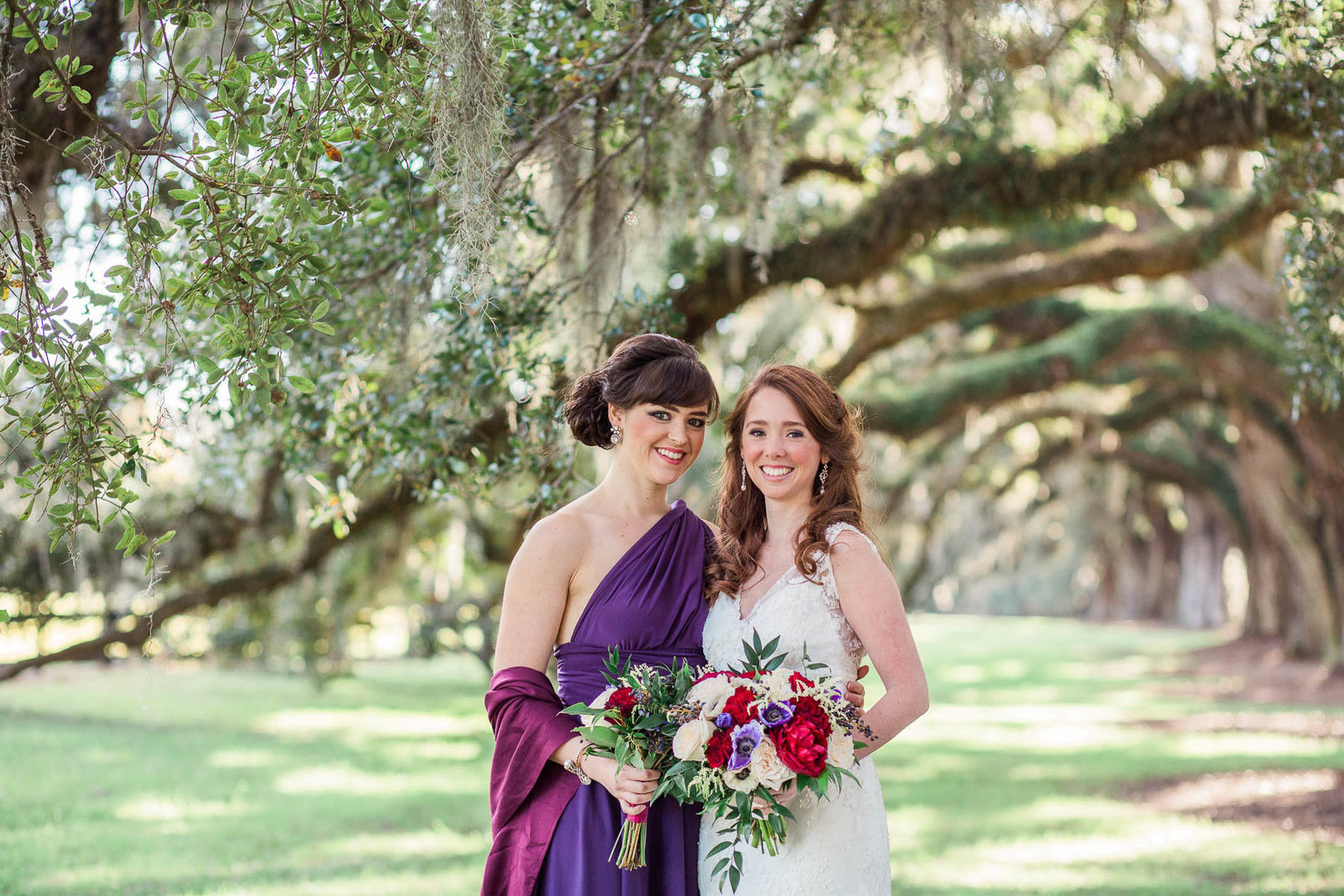 Bride and bridesmaids stand on avenue of oaks, Boone Hall Plantation, Charleston, South Carolina. Kate Timbers Photography.