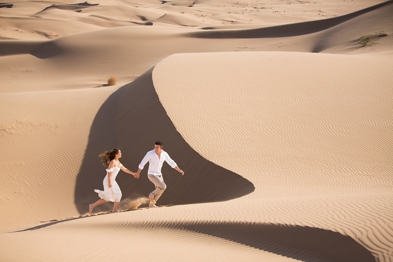 Bride and Groom Running in Epic  Glamis Sand Dunes Photo