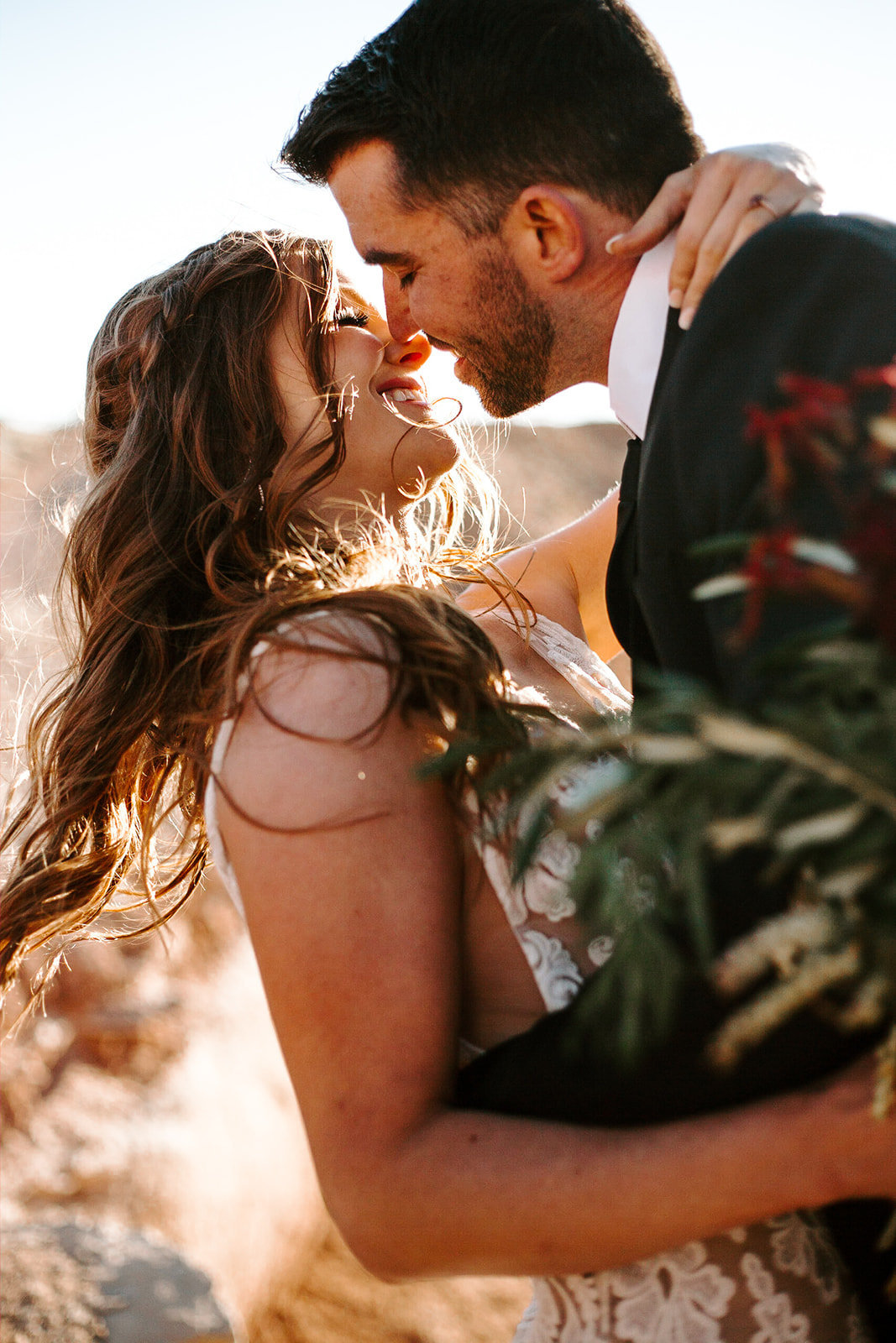 Couple with their faces together and the brides arm around the grooms neck during their Arizona Elopement