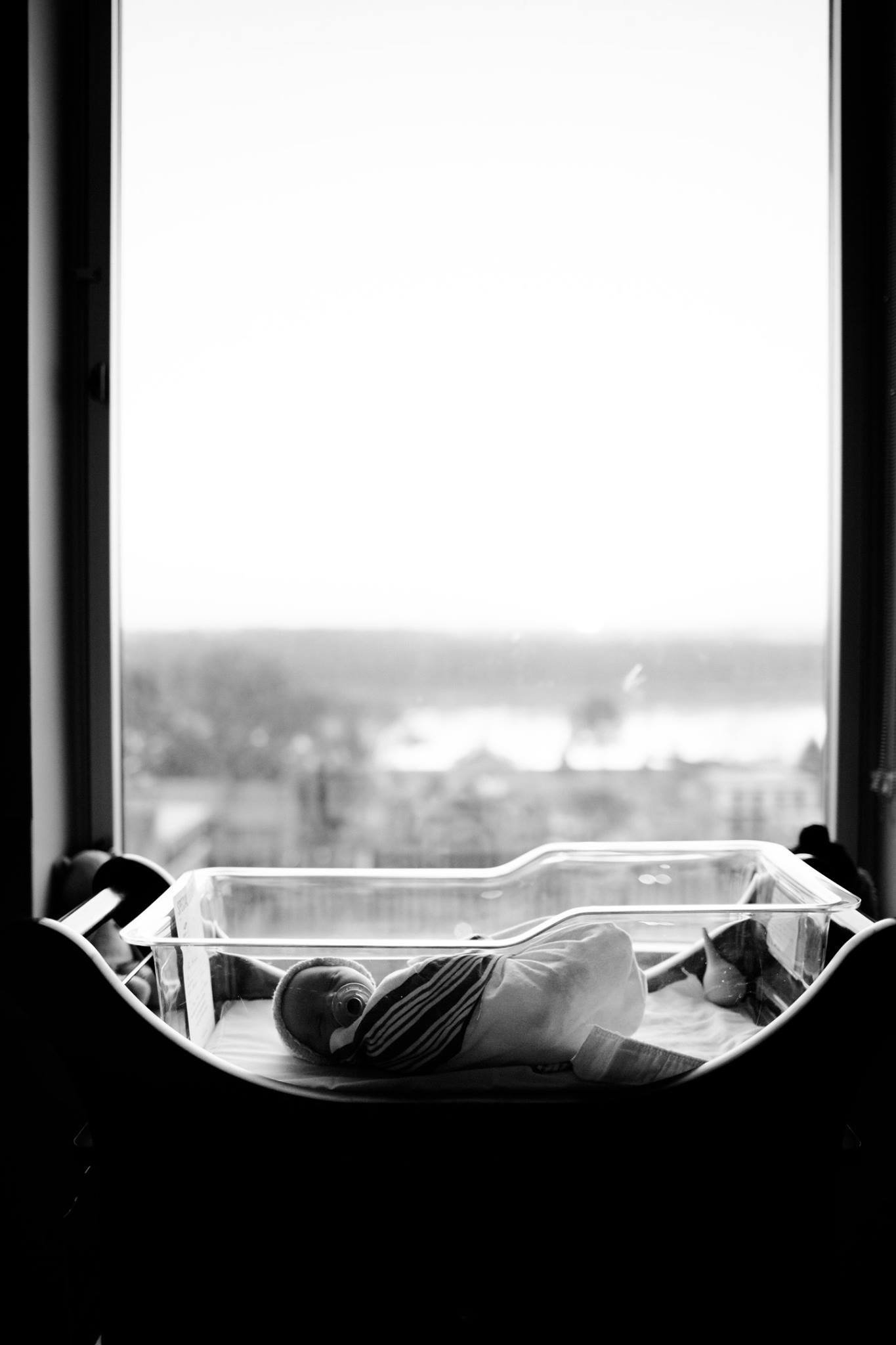 newborn laying in hospital crib next to window overlooking the streets of main street st charles missouri