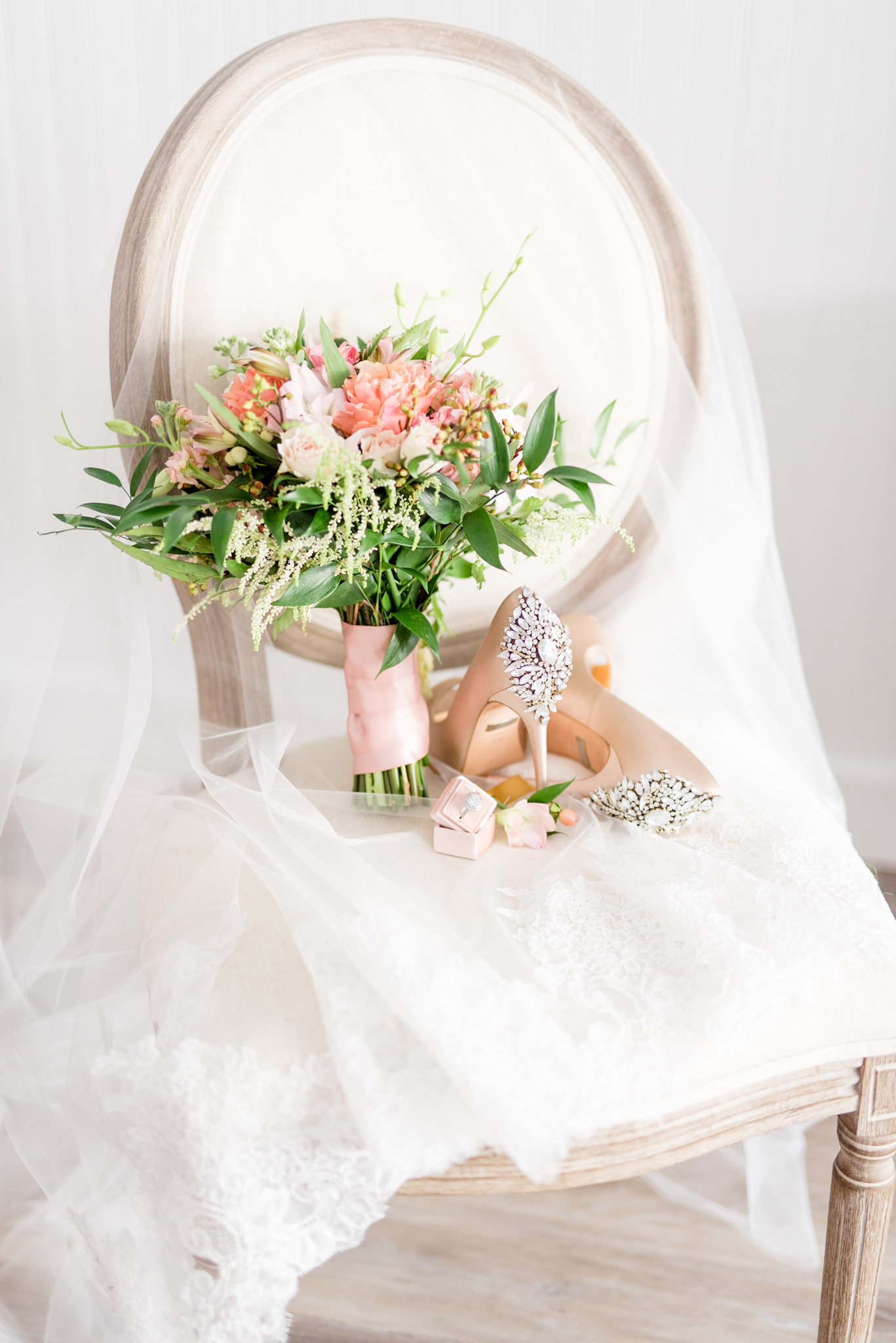 Wedding bouquet and shoes sit on veil and chair.