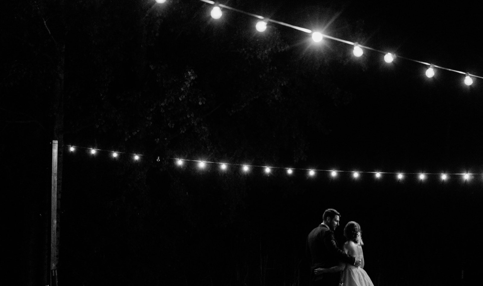 A bride and groom share a quiet moment together under bistro lights after their Leavenworth Washington elopement