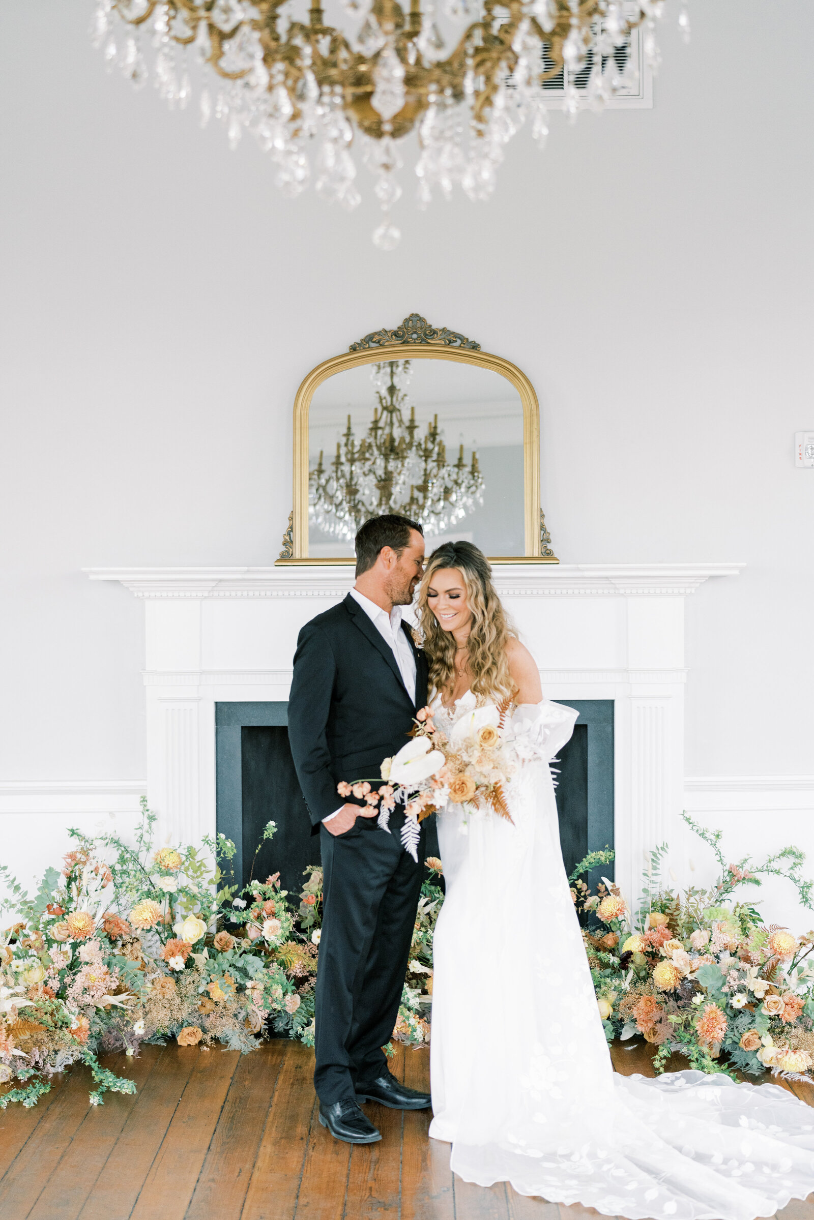 bride and groom standing in front of a fireplace with florals all around them laughing