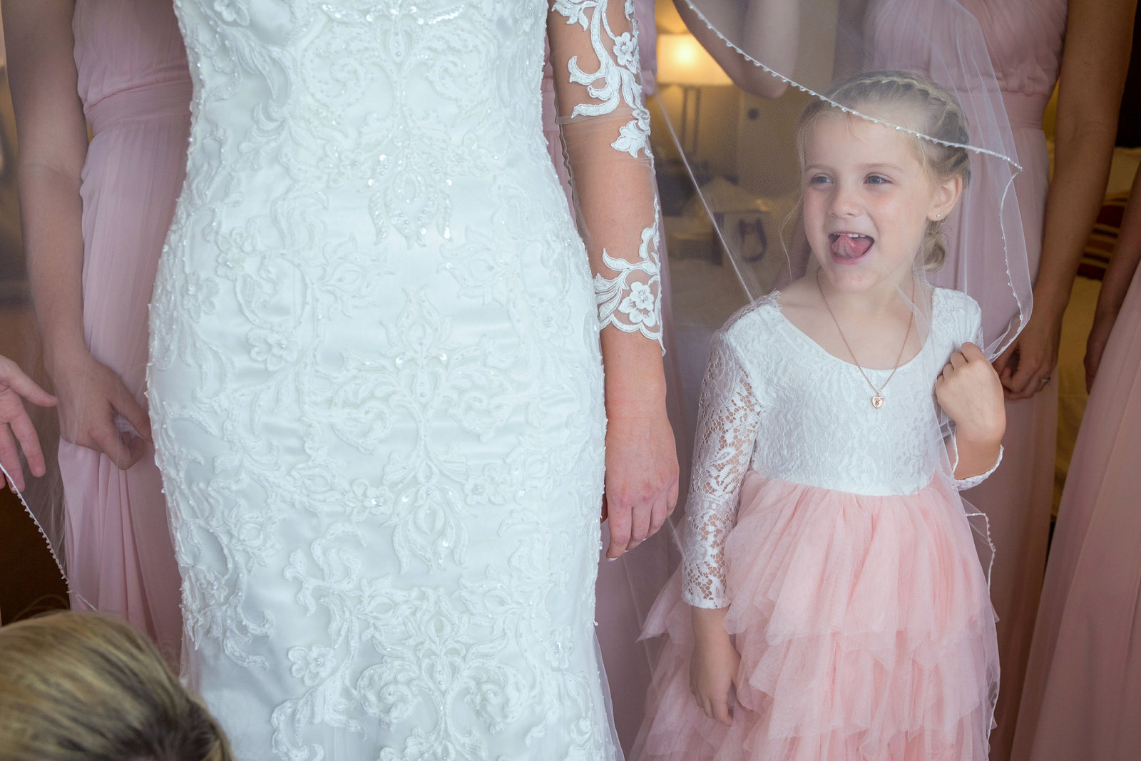 flower girl making a silly face while looking through brides veil
