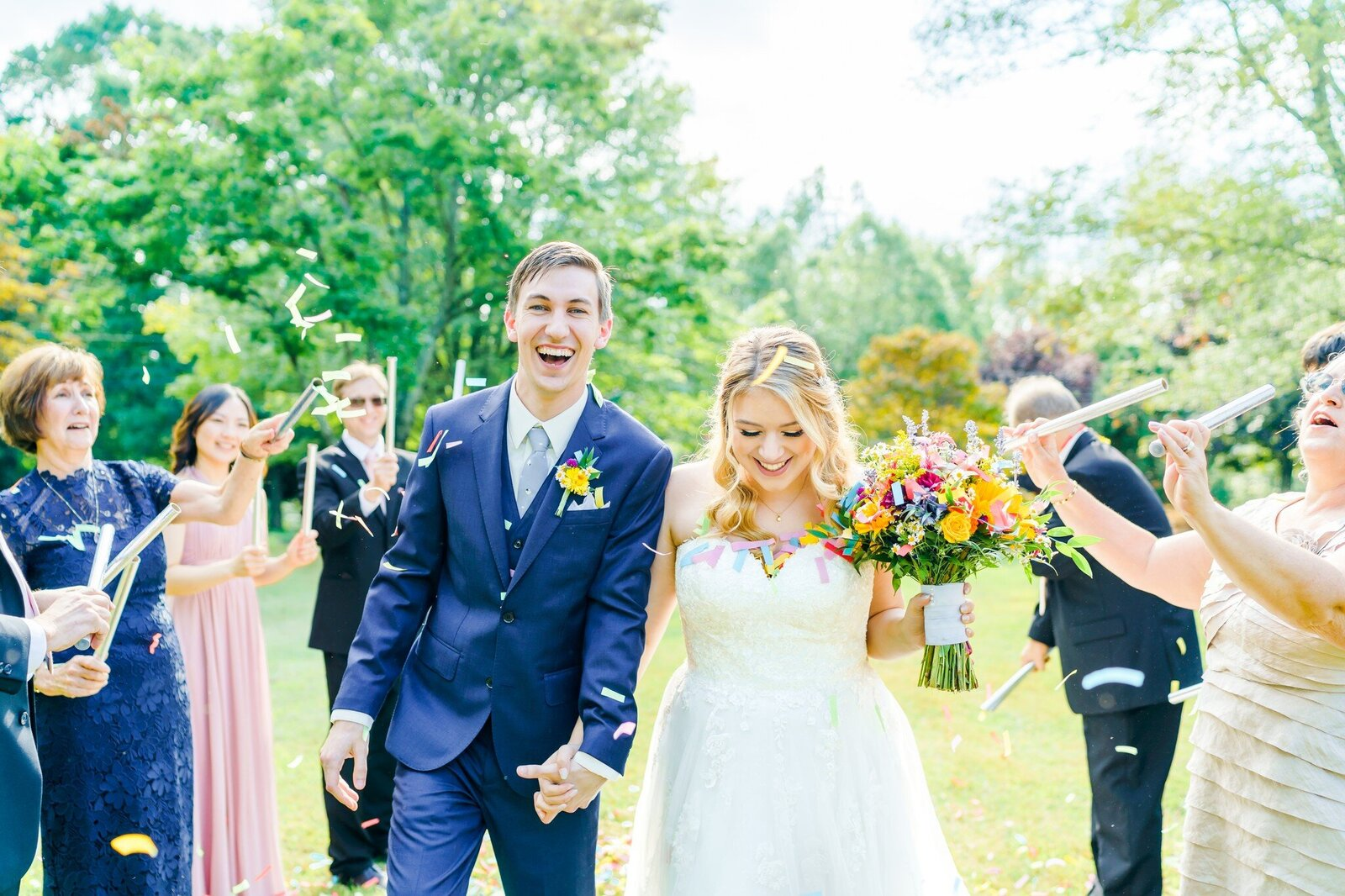 Bride and groom excitedly hold hands and walk down aisle of New Hampshire Wedding