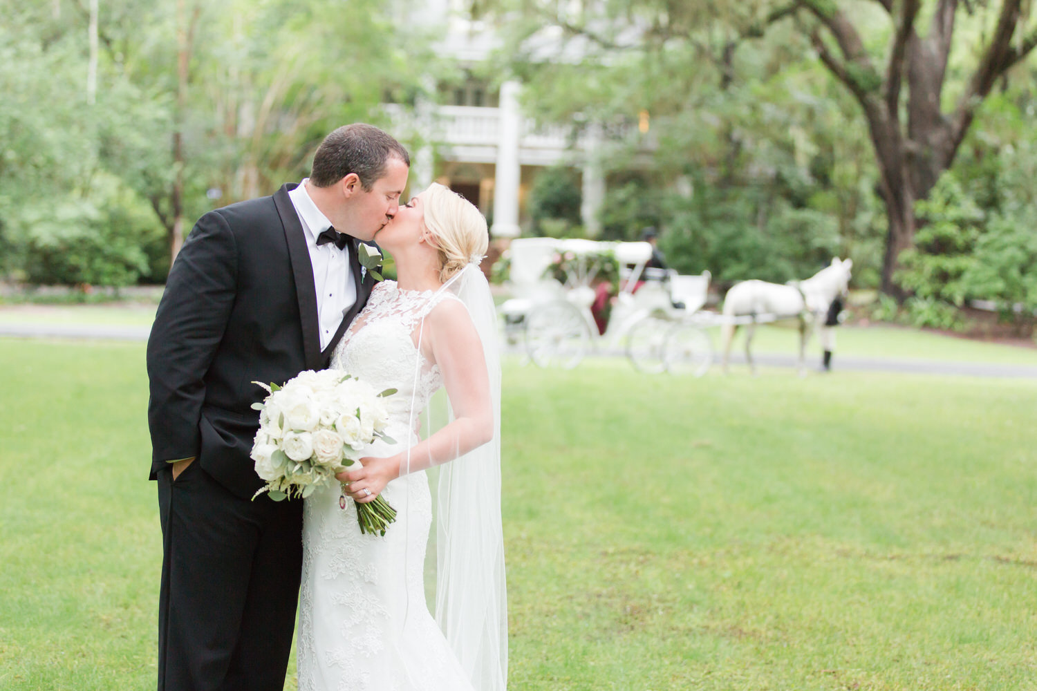 bride and groom kissing outside and holding flowers