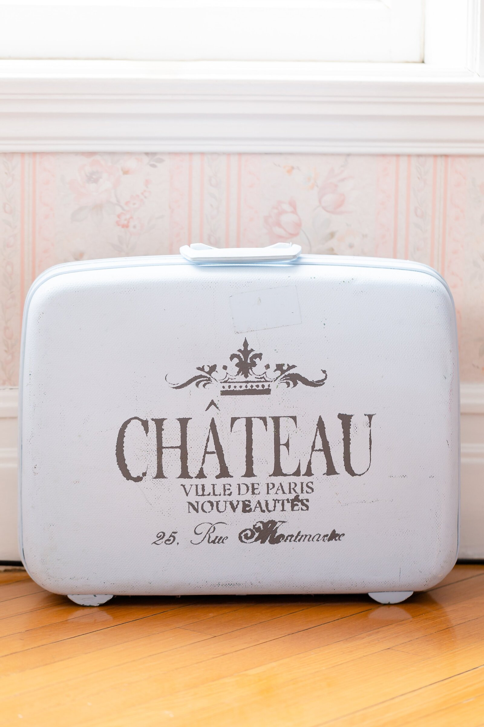 Vintage-white-suitcase-sitting-in-a-room-at-chateau-la-motte-in-woodstock