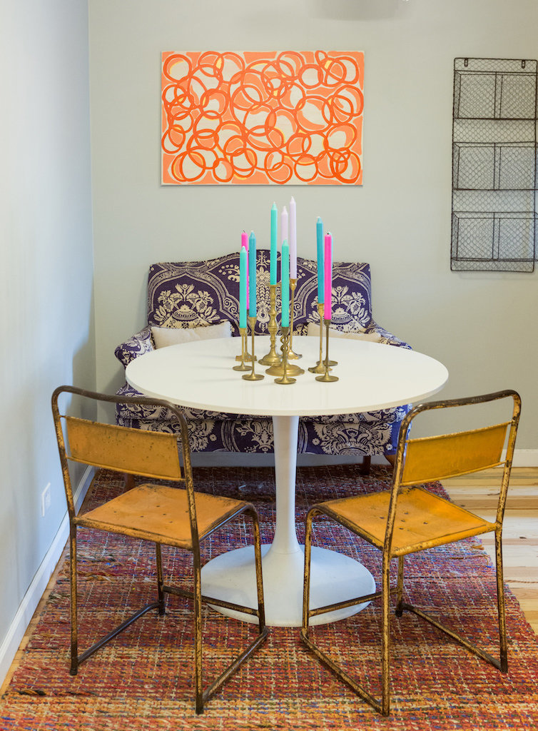 An eating nook with a white table with brass candlesticks and colorful candles.