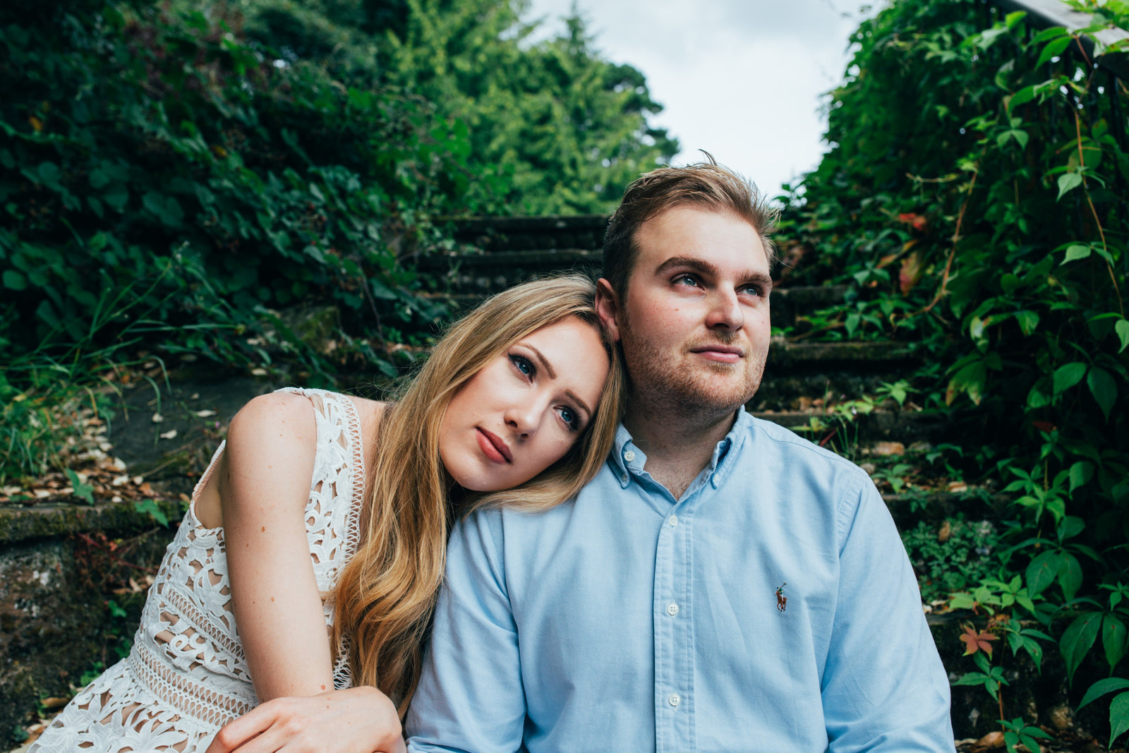 Photo of girlfriend leaning on boyfriend sitting on steps in leafy Suffolk