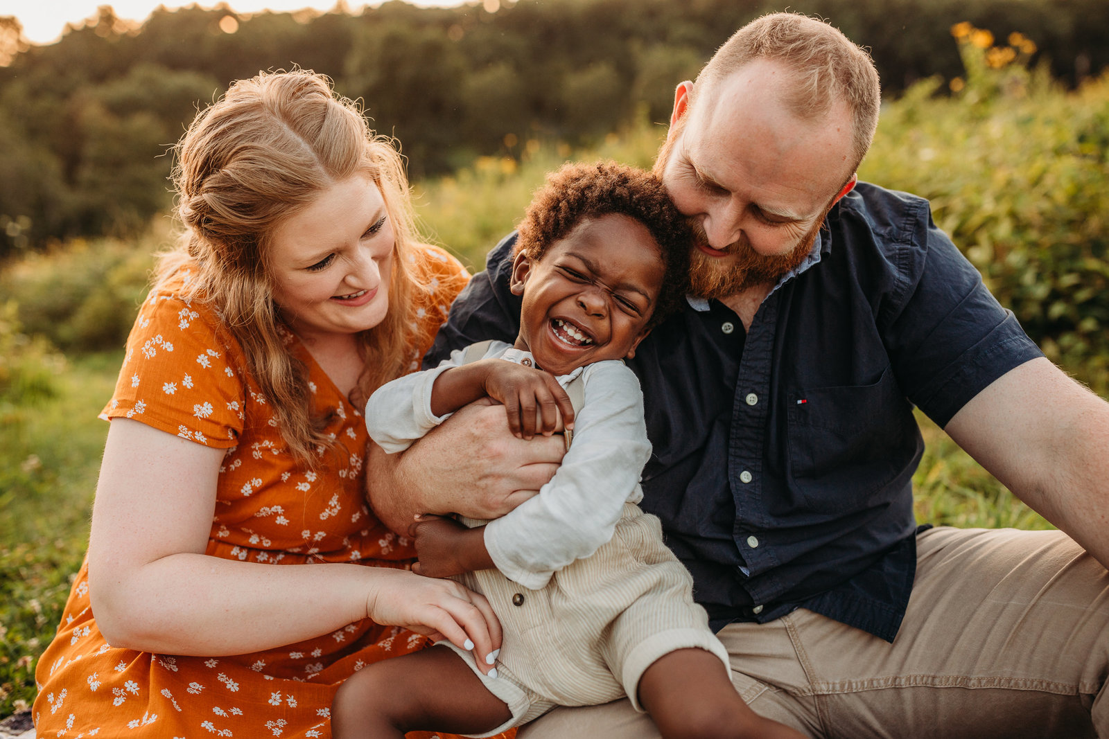family with adoptive son outdoors laugh on blanket during southborough family photos