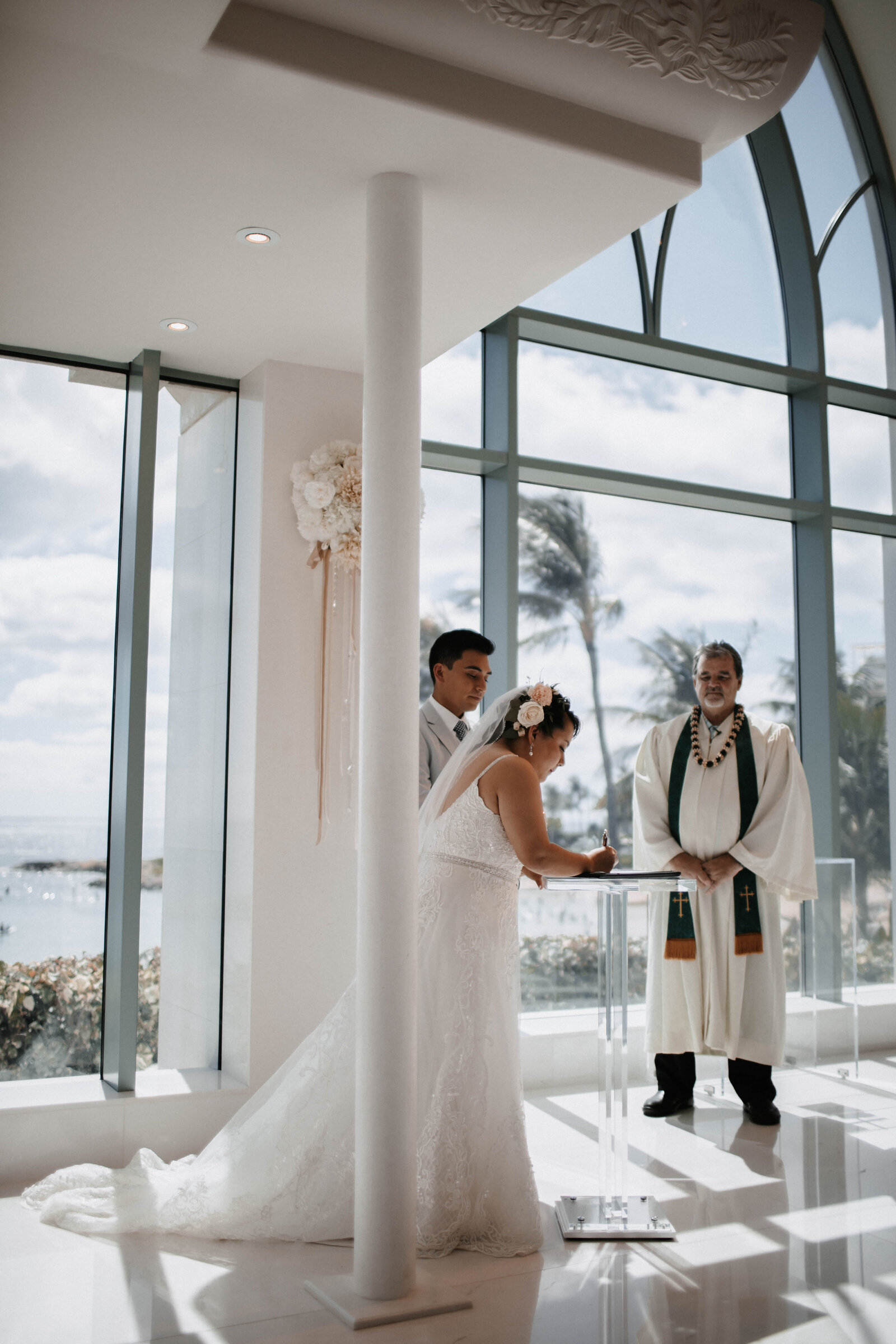 bride-and-groom-signing-marriage-certificate-in-glass-chapel
