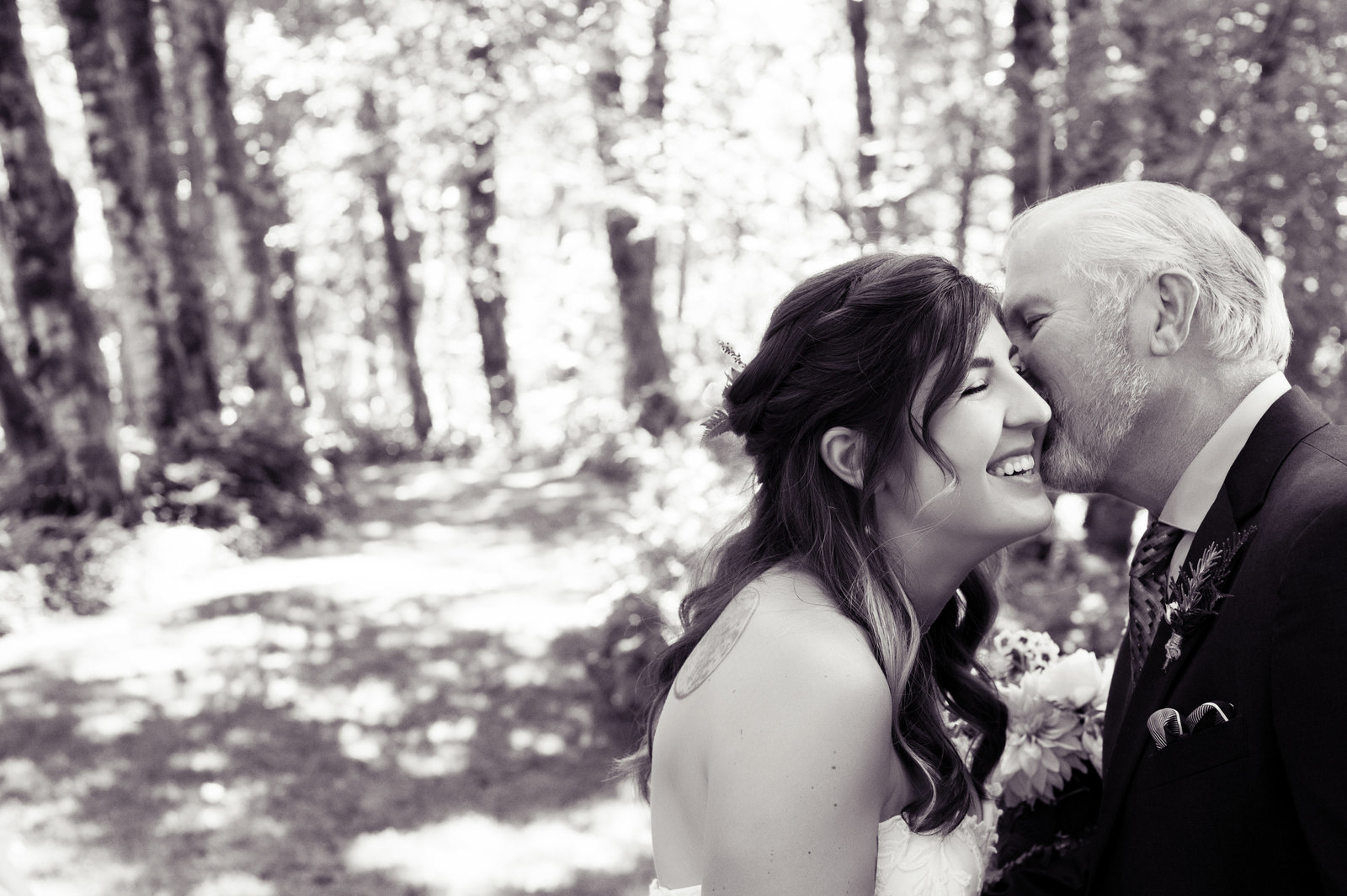 father of bride kisses daughter