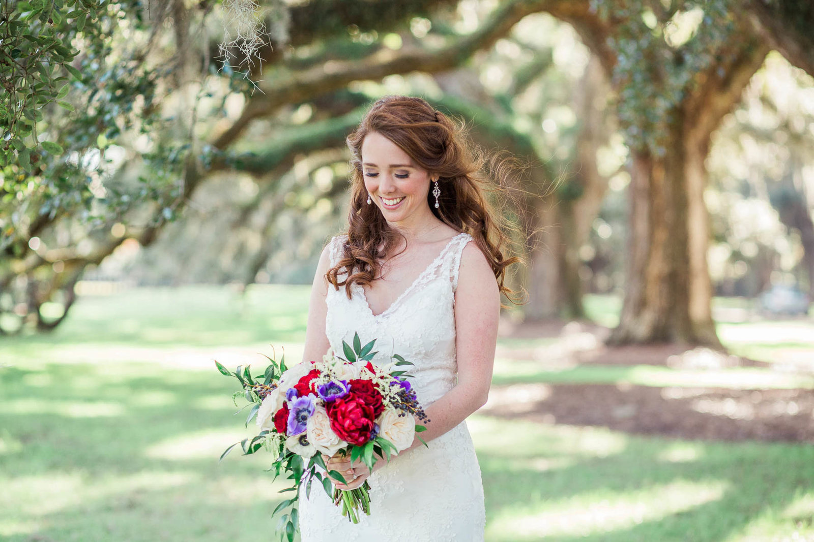 Bride stands under avenue of oaks, Boone Hall Plantation, Charleston, South Carolina