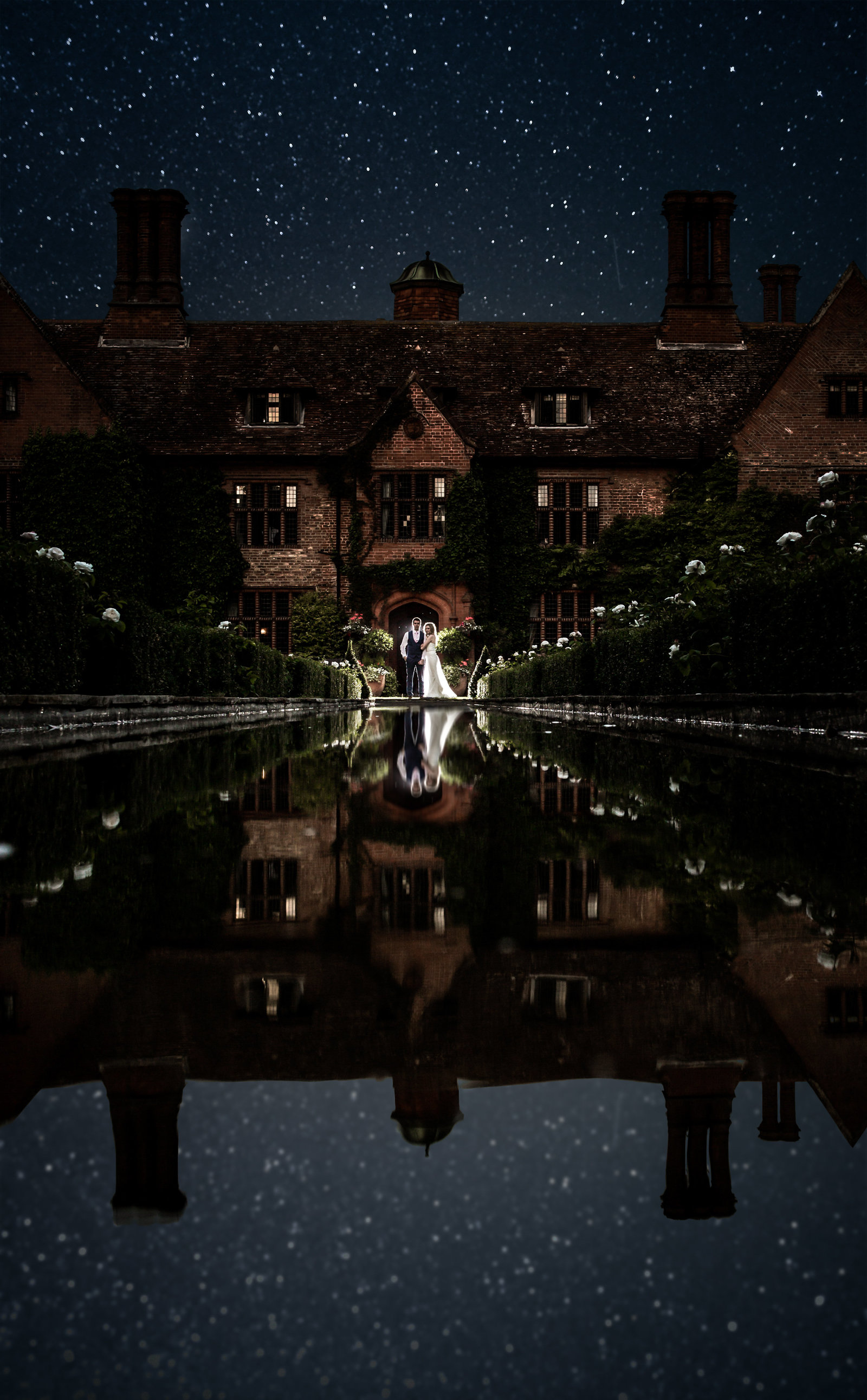 A bride and Groom stand and smile at each other in front of a manor wedding venue with a water way in front of them. Stars are in the sky and reflected in the water.