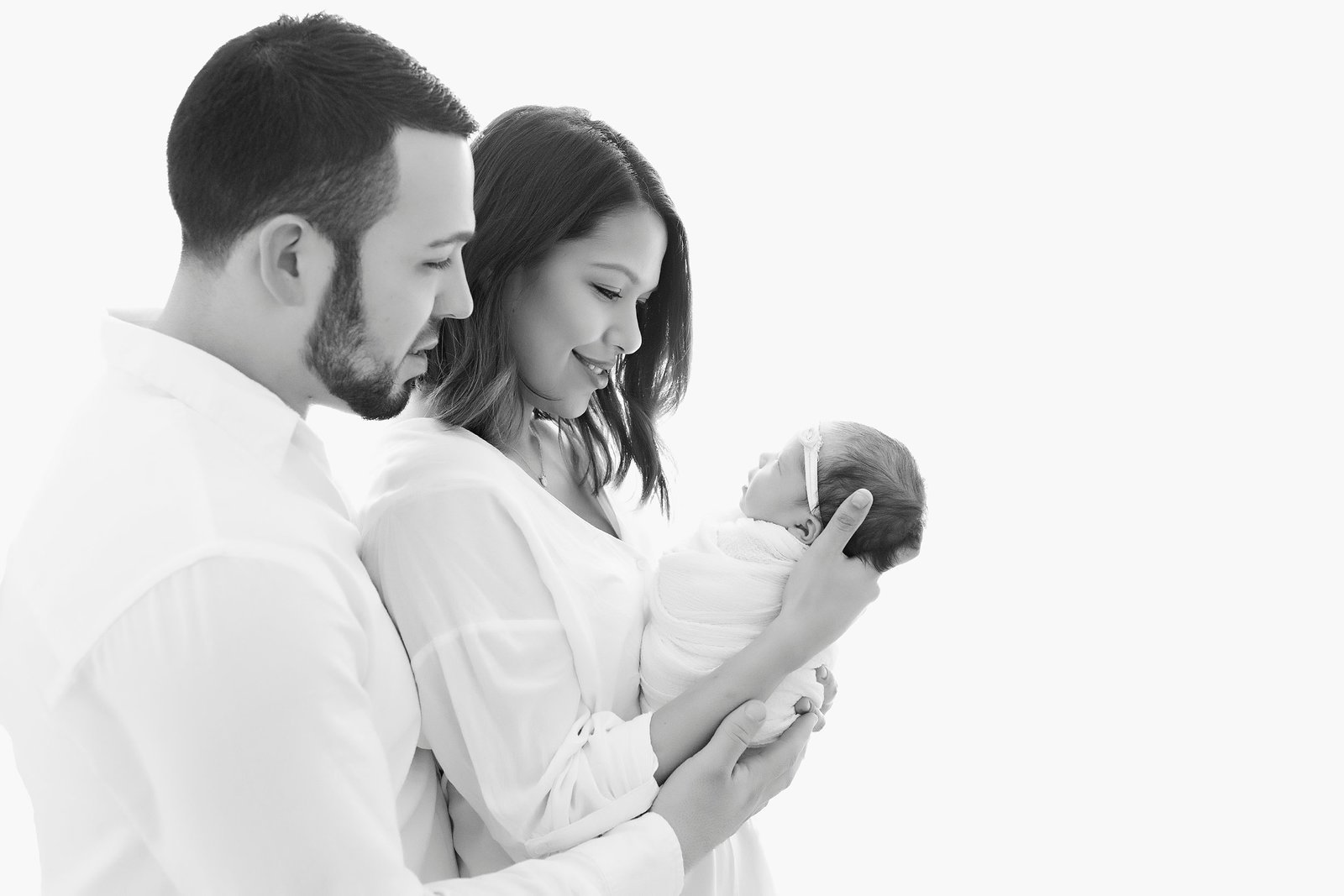 Black and white image of newborn and parents