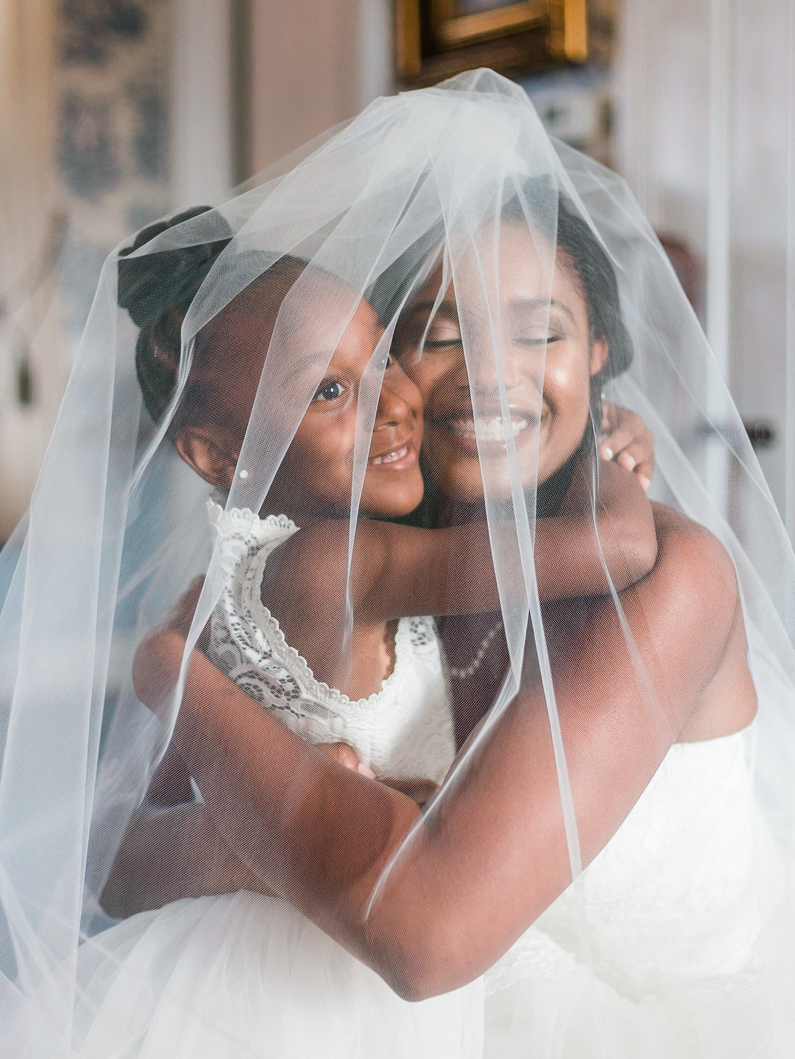 Bride and flower girl hug under veil