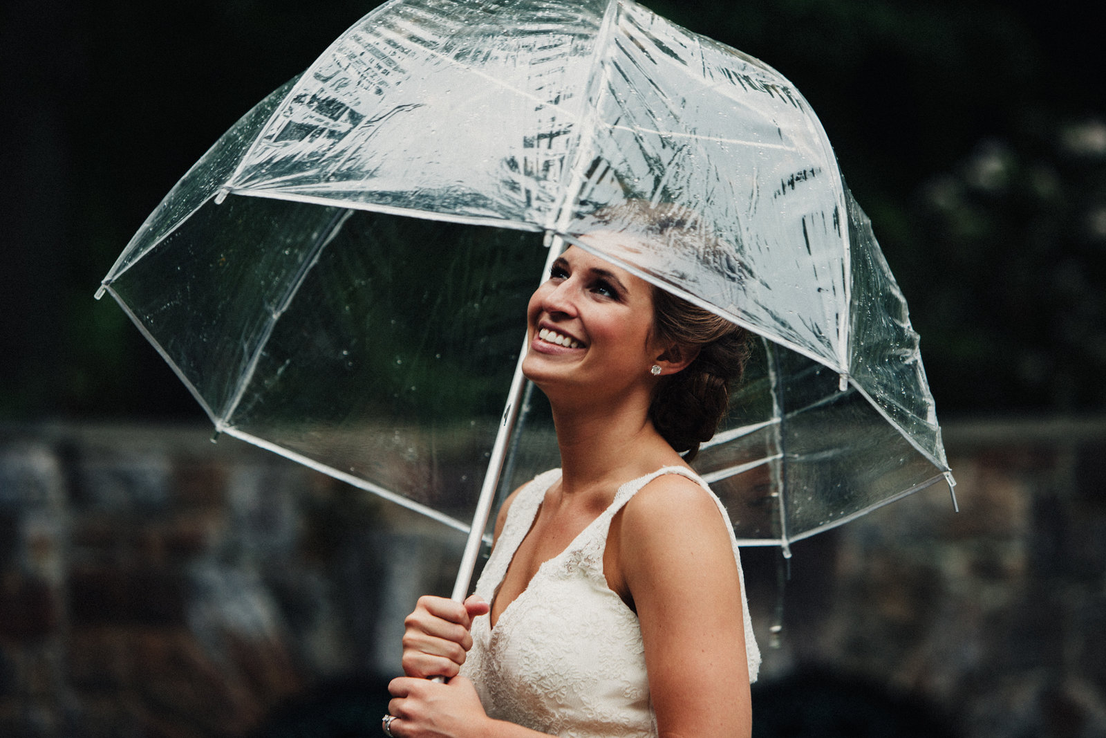 bride holding an umbrella outside at her wedding at winterthur musuem