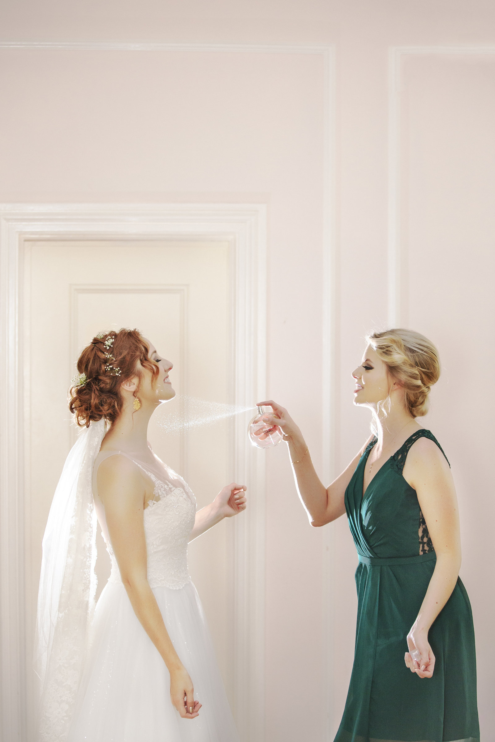 maid of honor spraying perfume on the bride