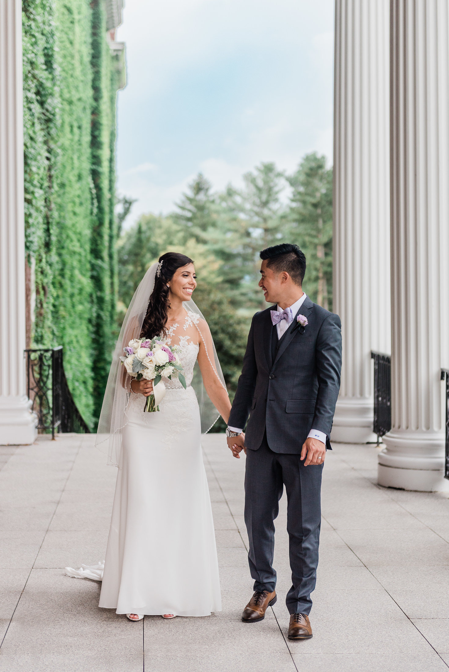 A couple strolls the grounds of the college of the holy cross after their wedding ceremony