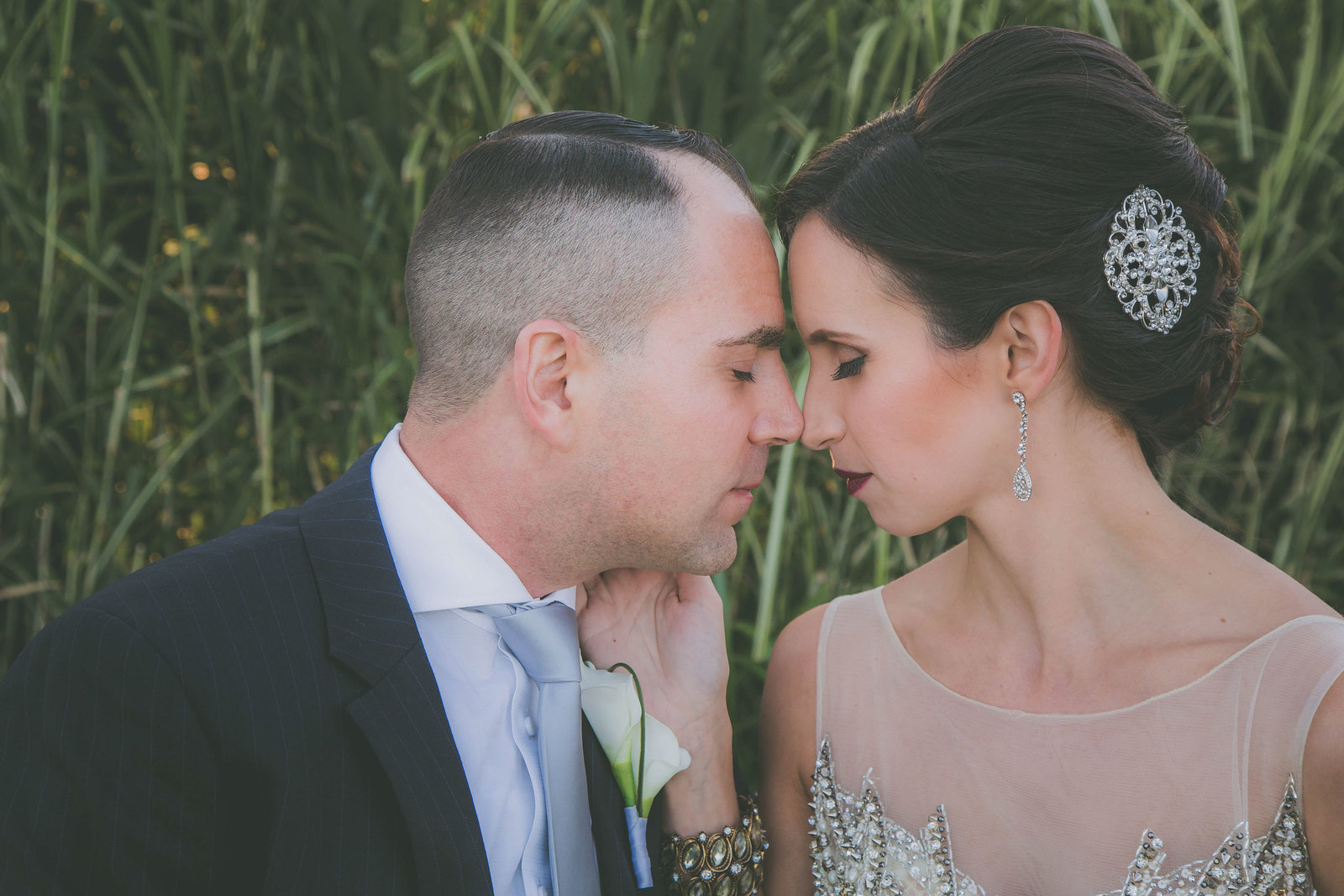 East Coast bride and groom go forehead to forehead against tall grass.