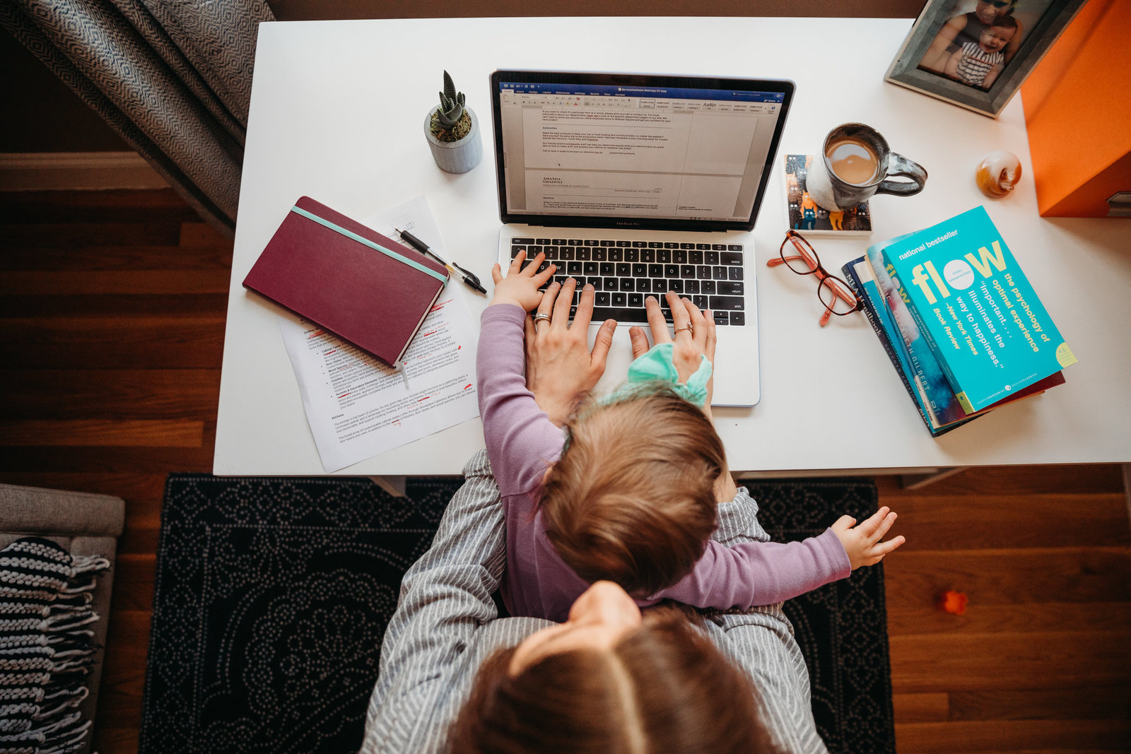 overhead image of mother working on computer with daughter in lap