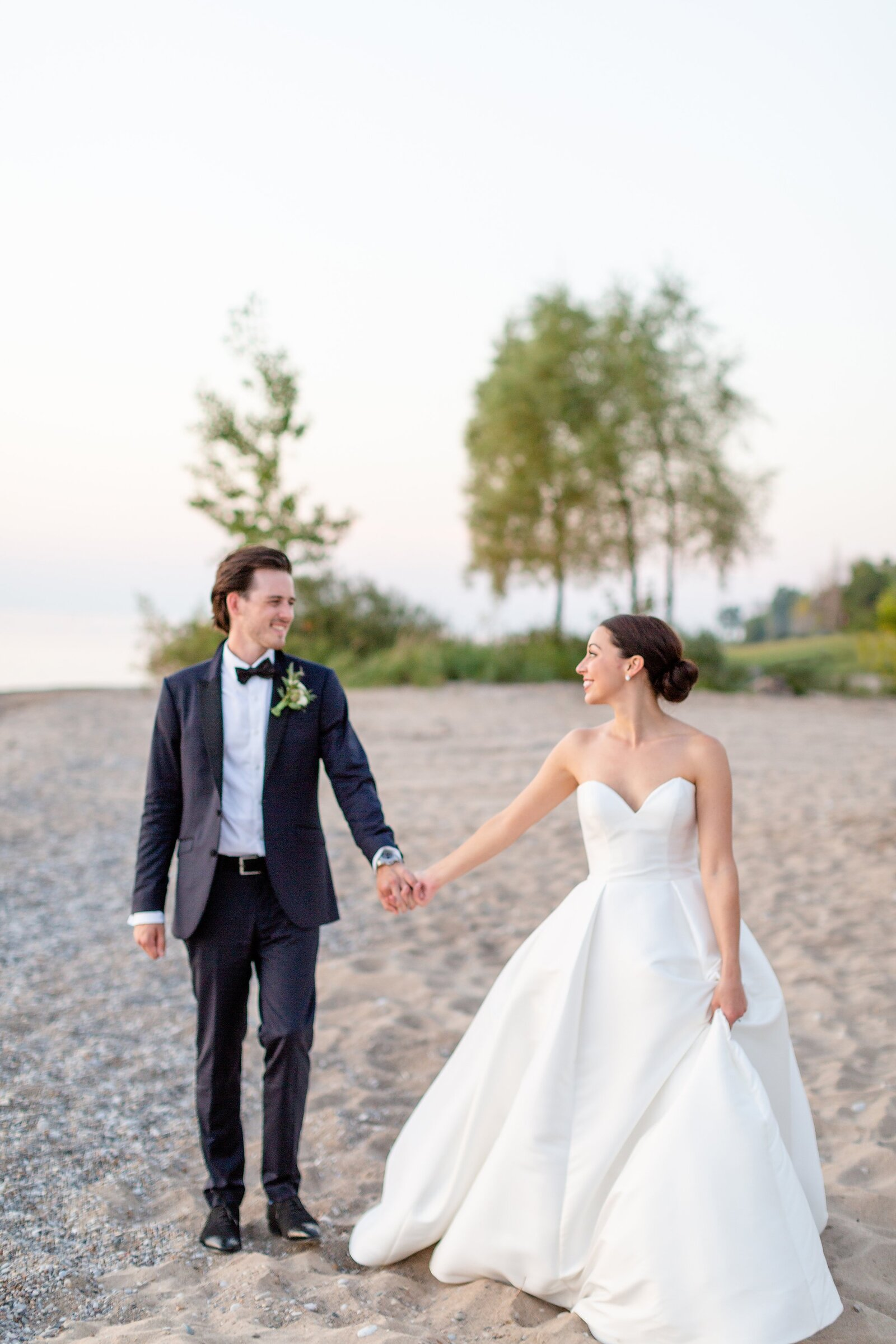 Bride-looks-back-to-her-new-husband-on-their-wedding-day-as-they-walk-along-the-beach-during-sunset-in-Zurich-Ontario
