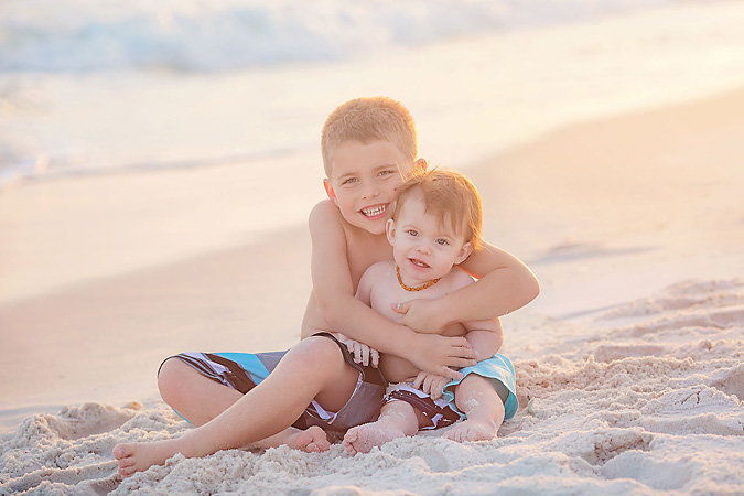 young brothers hugging while sitting in the sand at the beach