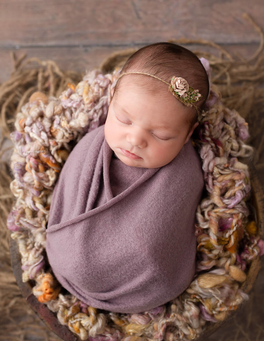 Cute newborn girl wrapped in a wooden bowl.