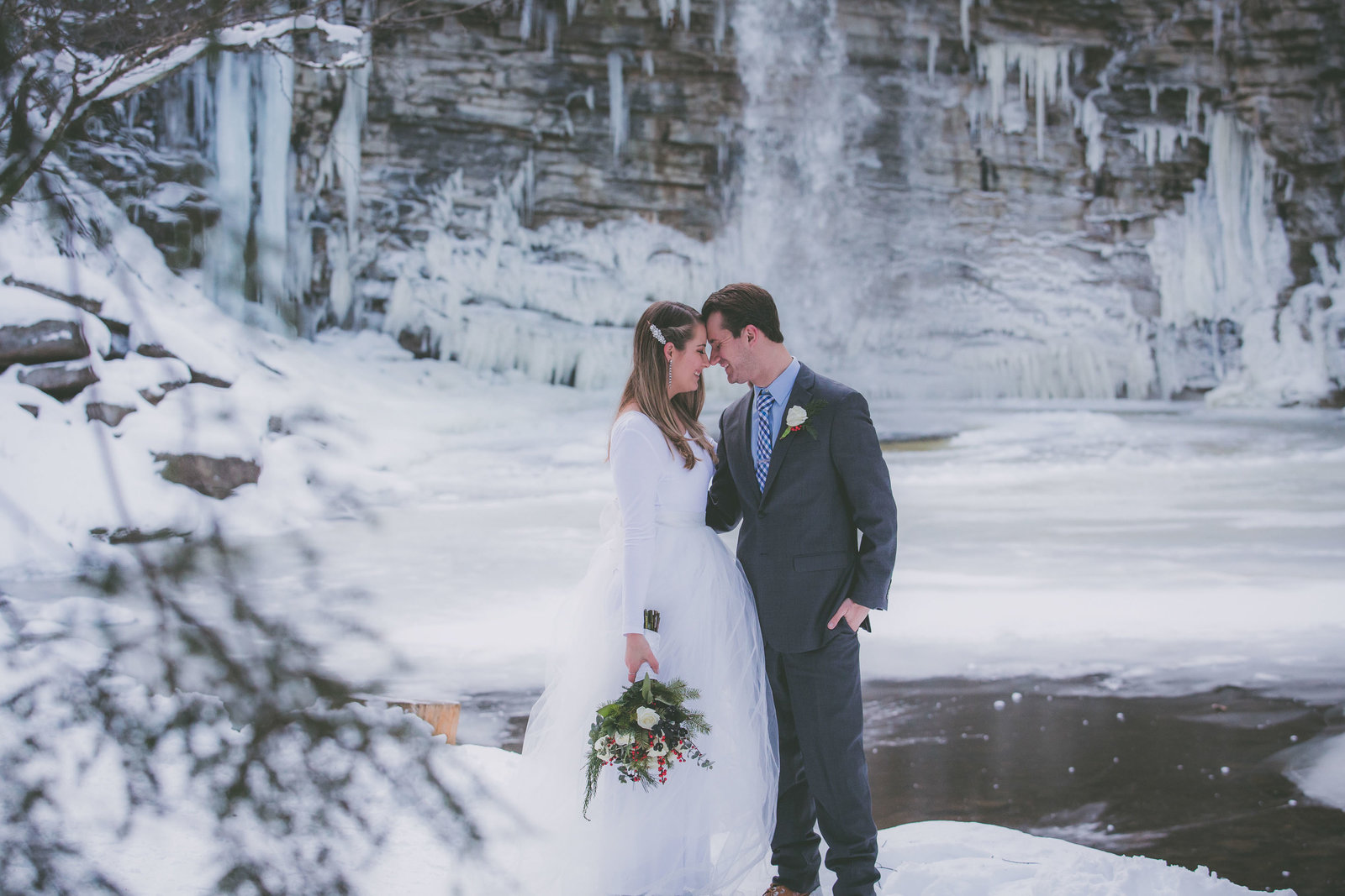 Couple touches foreheads with waterfall view in winter surrounded by snow.
