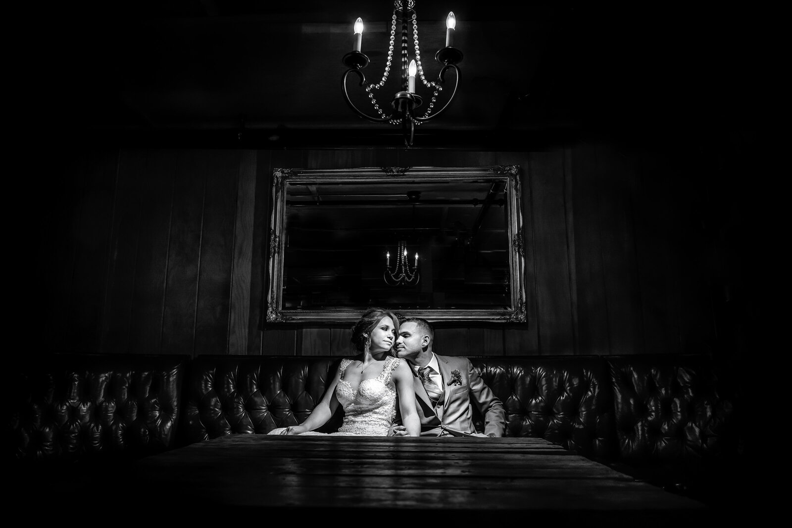 black and white photo of bride and groom spotlit on a couch at perona farms