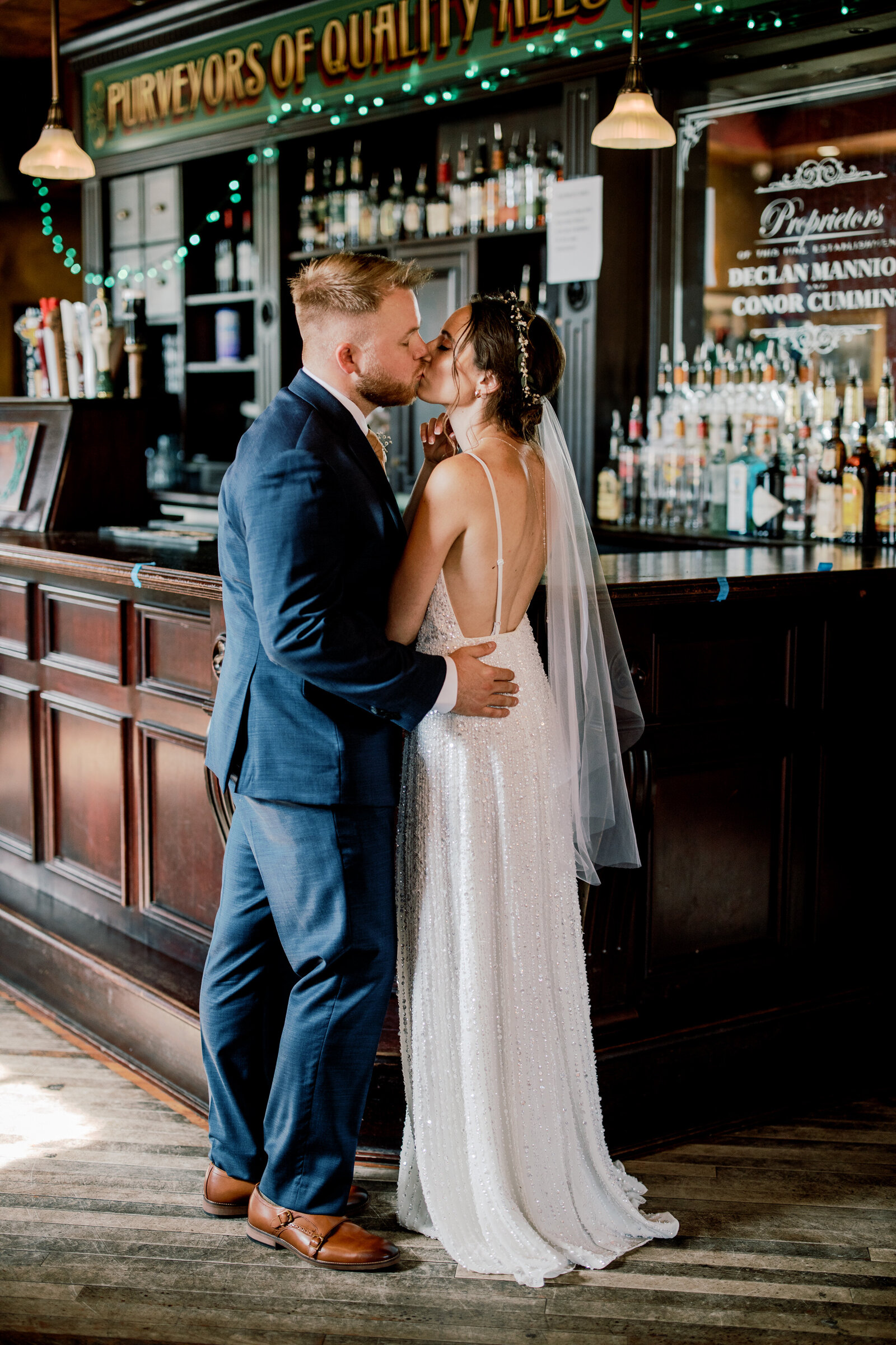 bride and groom kissing at old bar