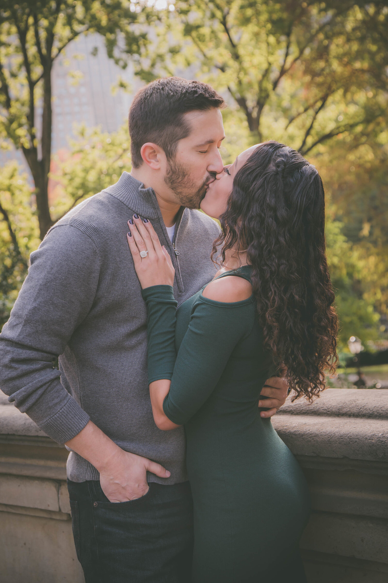 Couple kisses in Central Park NY during engagement session.