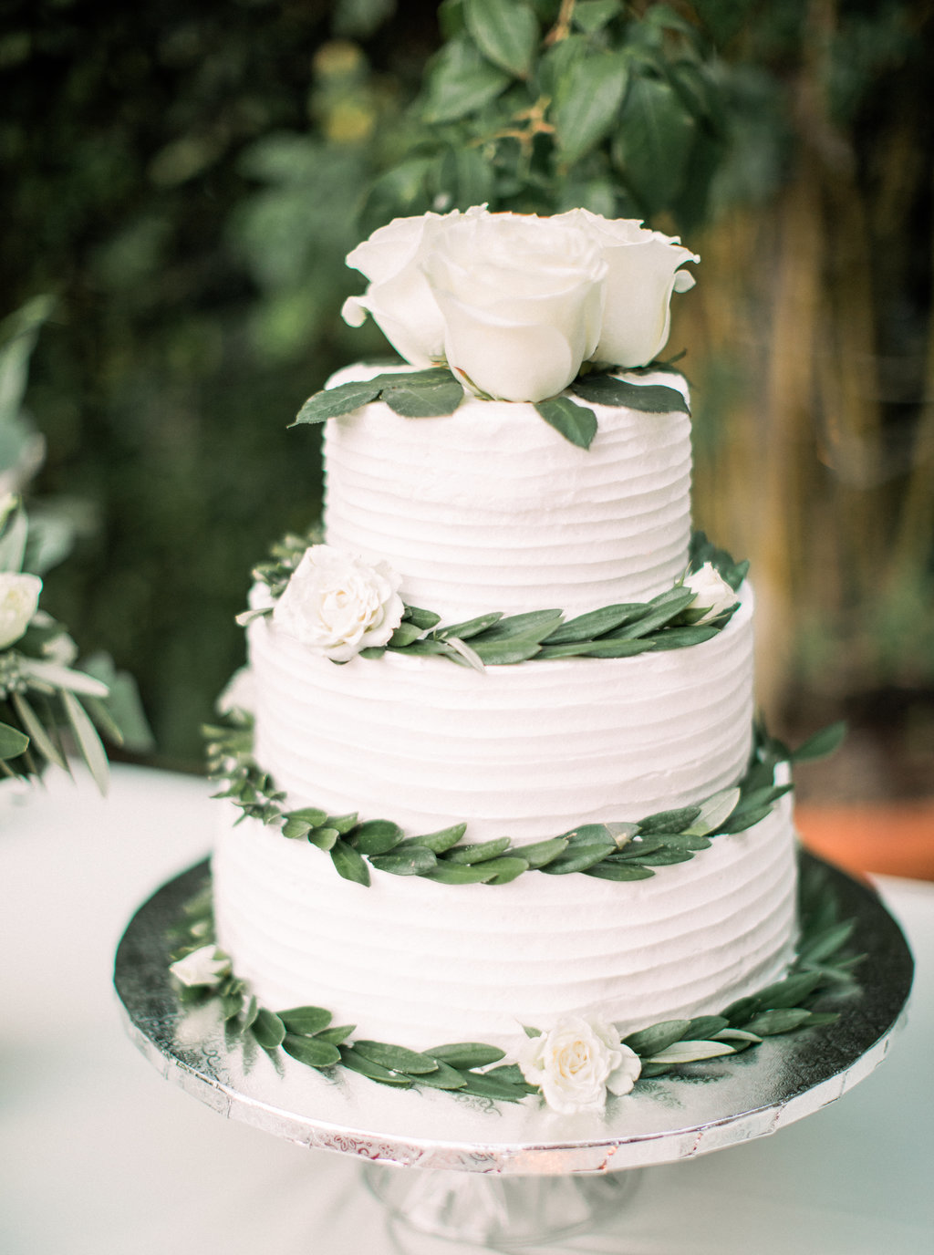Three tiered wedding cake with eucalyptus leaves at wedding reception at Butterfly Lane Estate