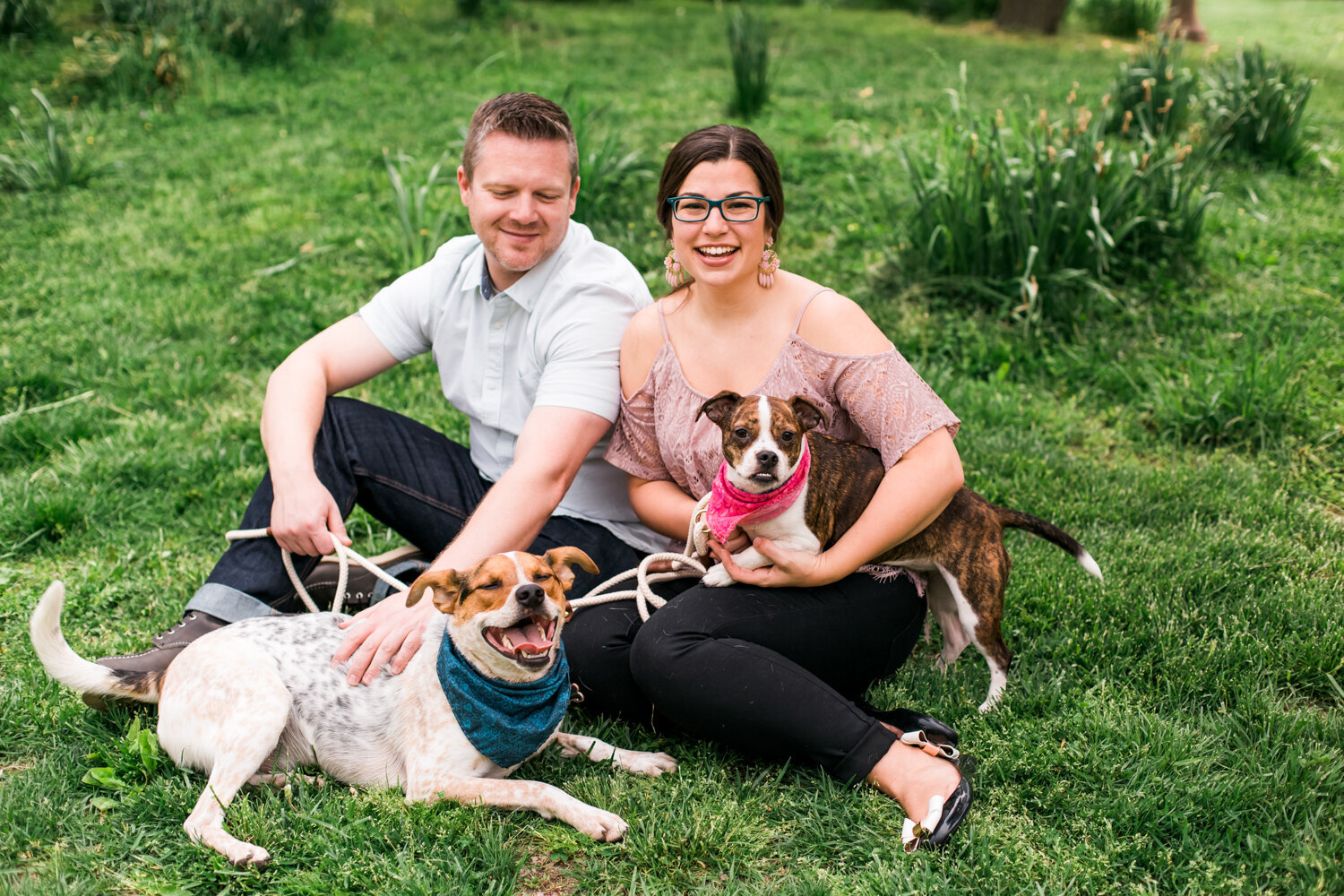 Engaged couple poses with their dogs for engagement photos in Tower Grove Park in St. Louis