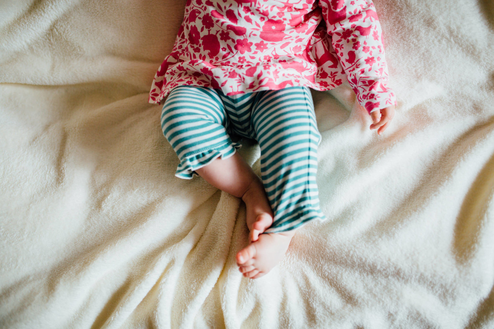Toddler legs and toes laying on a white blanket