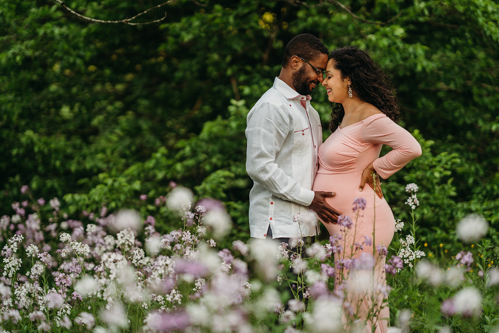 pregnant couple in a field of wildflowers