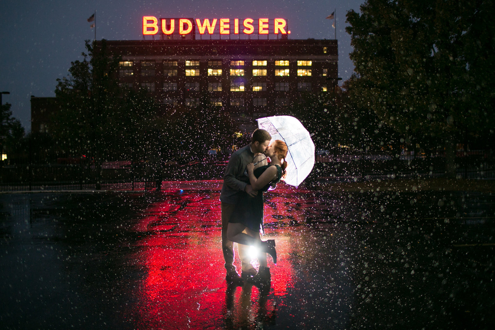 Engagement photo of Kailyn and Adam at night in the rain under a clear umbrella with the Budweiser building in the background.