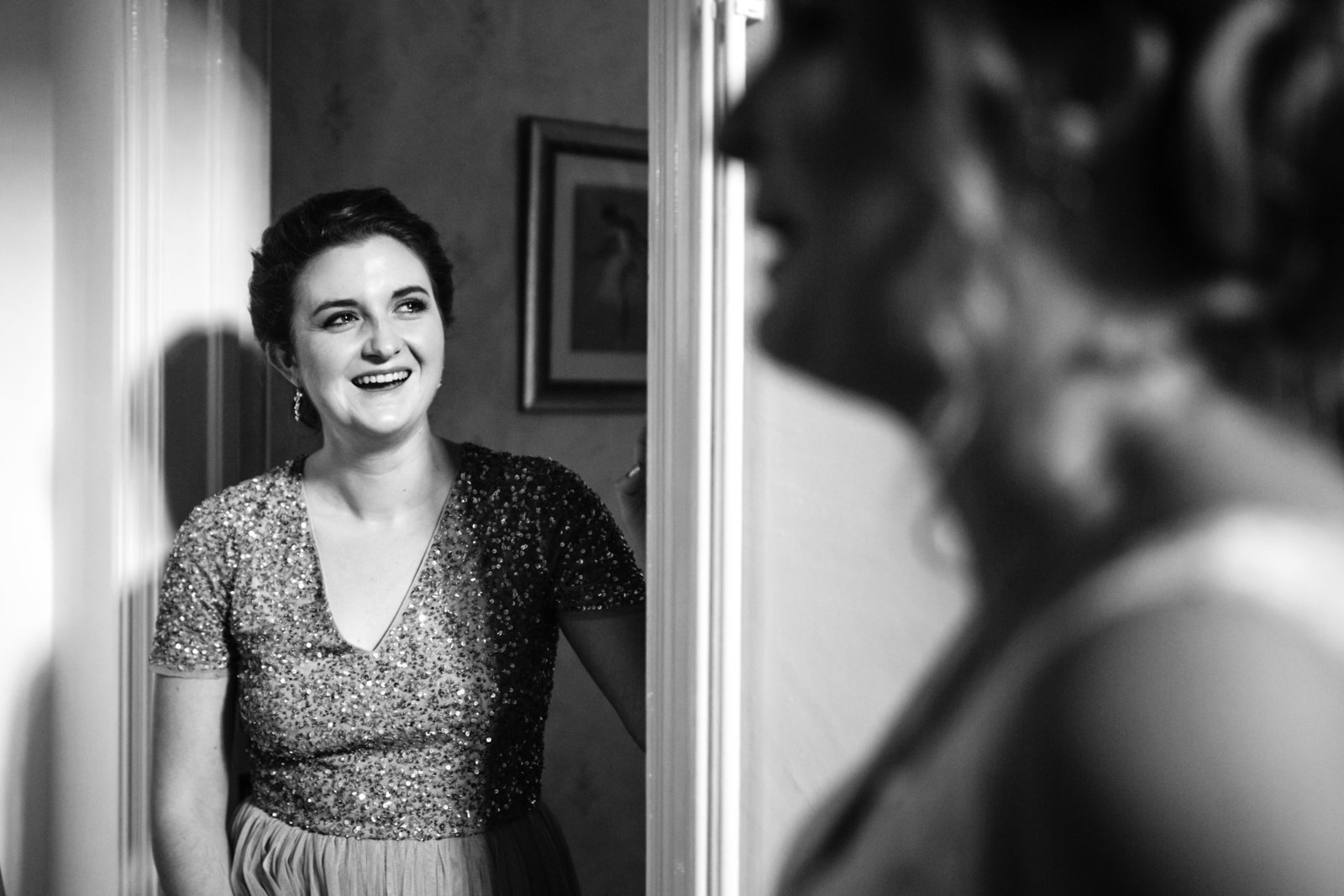 Bridesmaid sees her Sister in her wedding dress for the first tiem, she smiles and has a happy tear in her eye.
