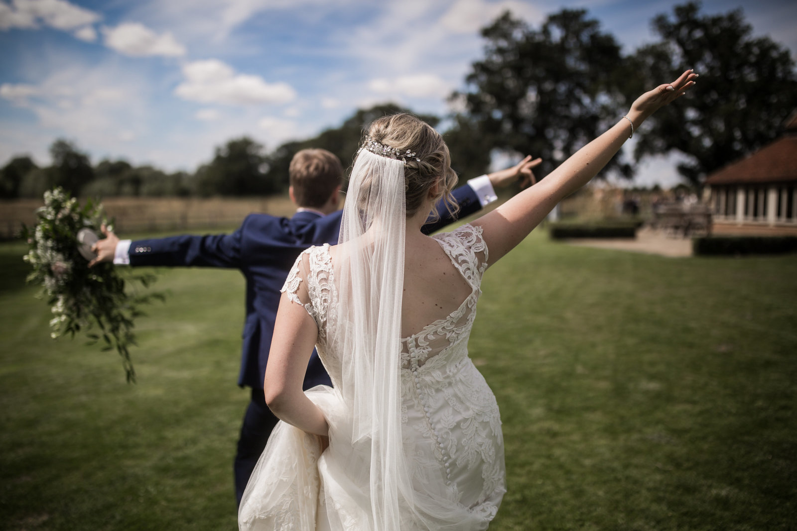 Bride and Groom arrive at their Norfolk wedding venue with their arms thrown in the air and their backs to the camera.